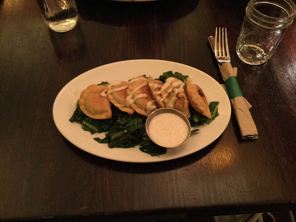 Five potato pierogies with a cashew cream drizzle on a bed of sauteed kale.