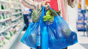 person walk through supermarket with items in two plastic bags