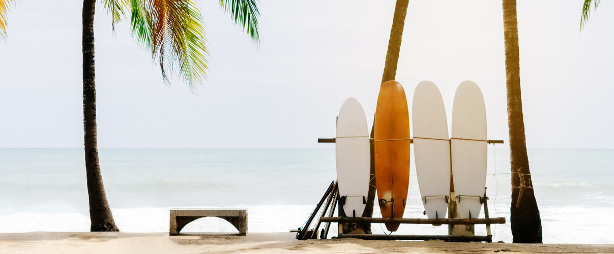 Surfboard and palm tree on beach backgro