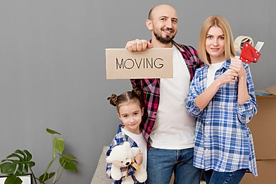 A young family on moving day holding up a moving sign after they secured mortgage advice from their mortgage broker DJB Mortgages Based in Chichester West Sussex