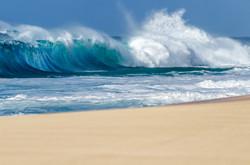 Big breaking Ocean wave on a sandy beach