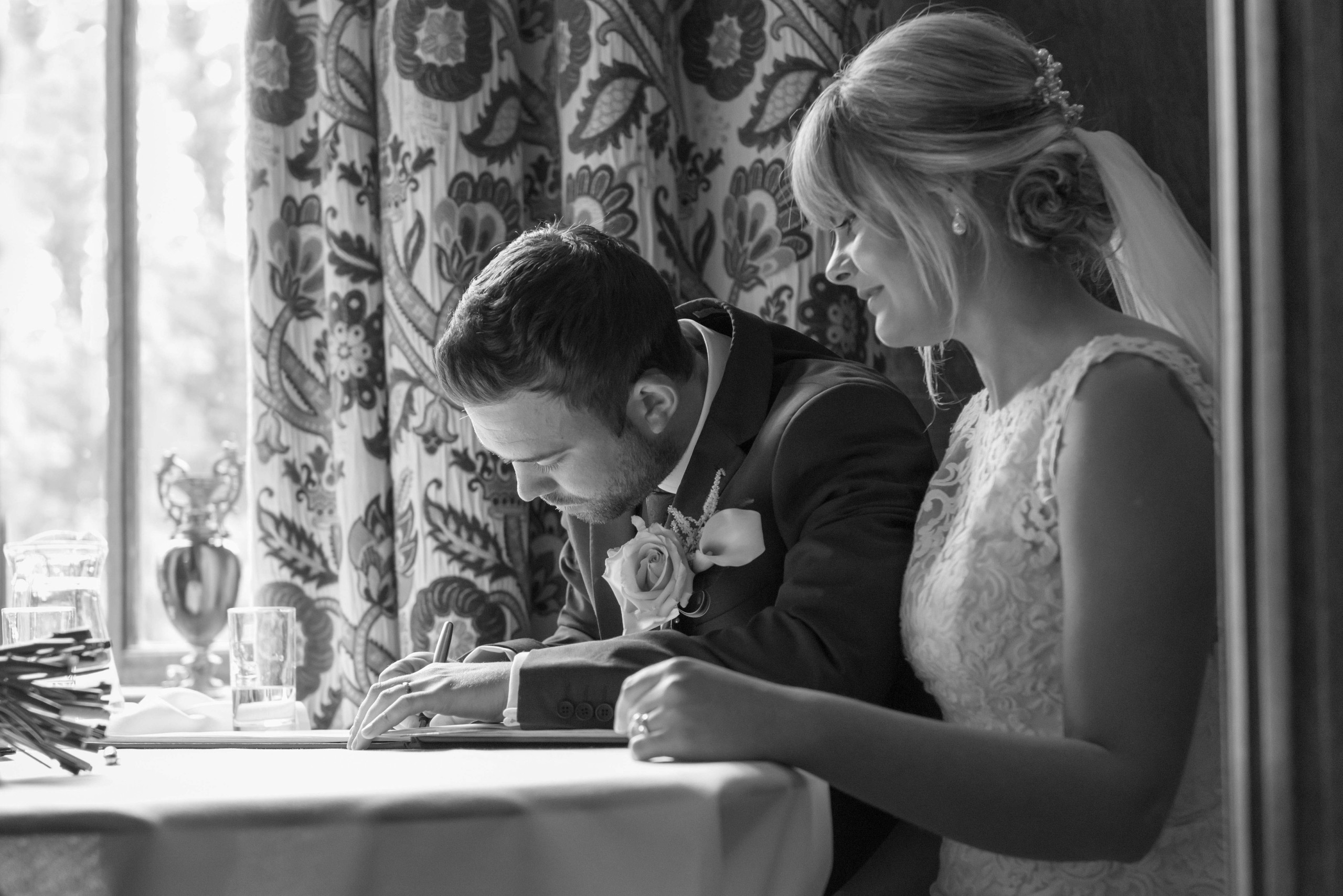 Black and white monochrome candid wedding photograph of bride and groom as groom signs register during wedding ceremony on wedding day at Ellingham Hall wedding venue in Northumberland