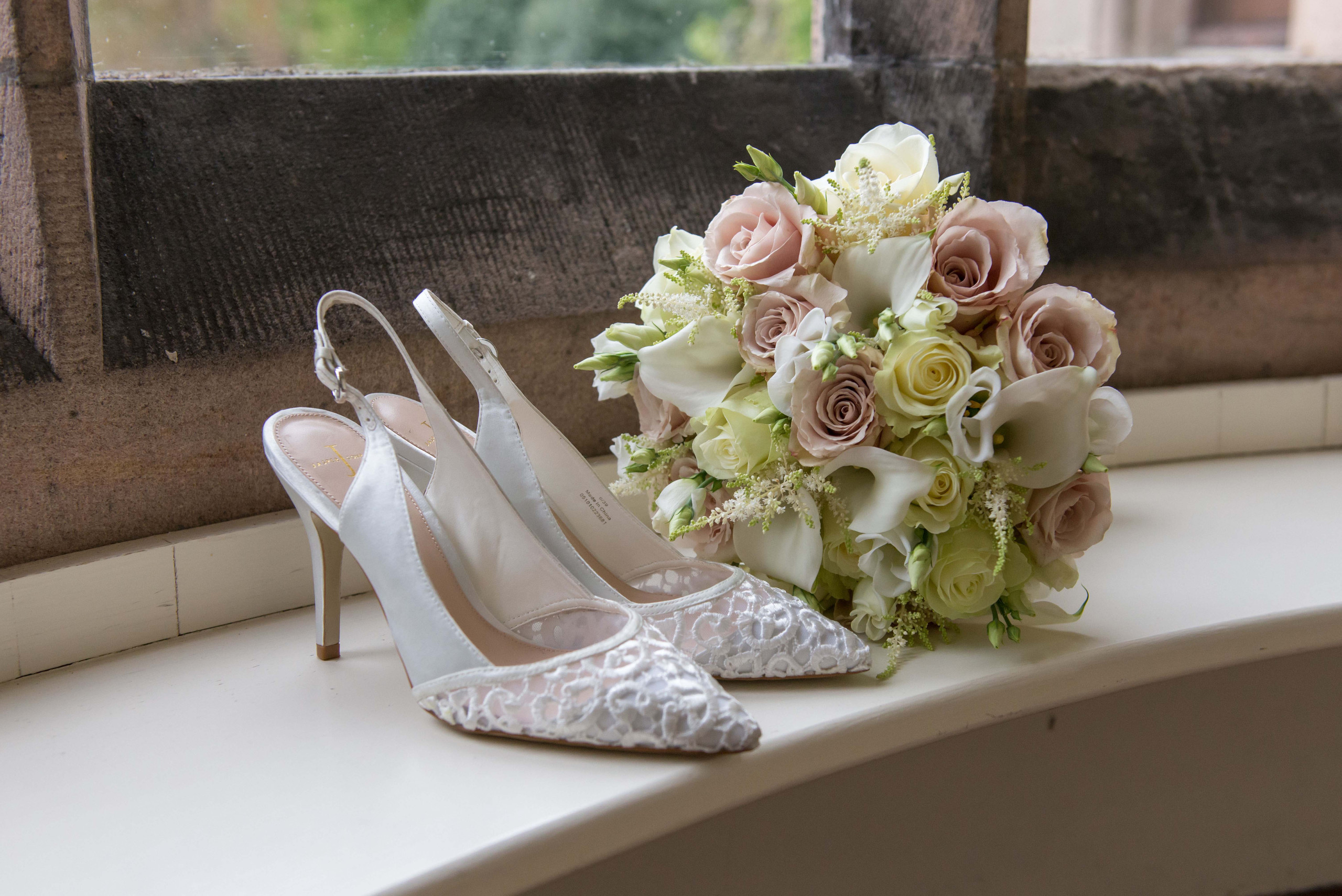 Photograph of bride's bridal bouquet with boho natural dusty pink flowers with white lilys, and white wedding shoes at Ellingham Hall venue in Chatham in Northumberland