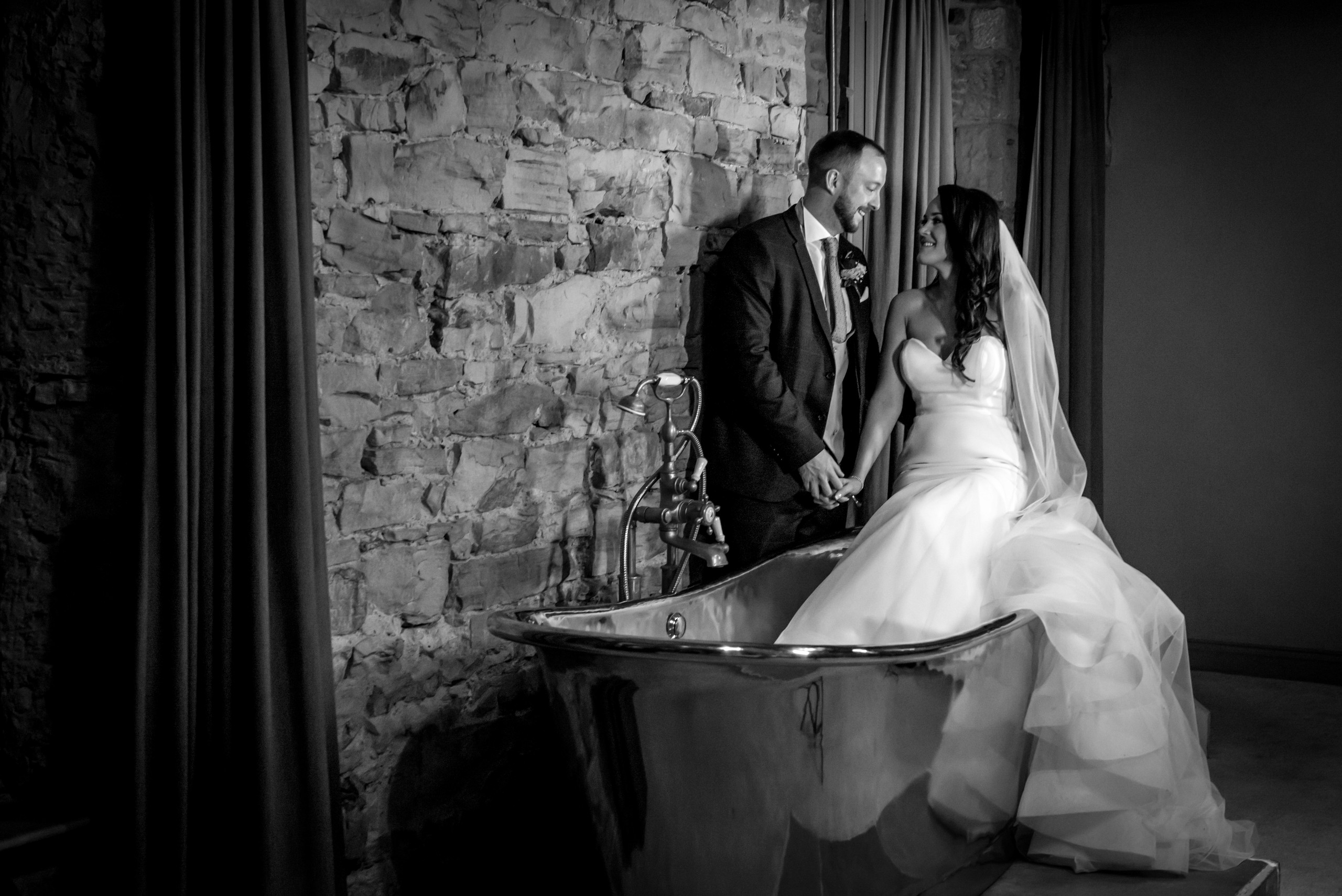 Black and white monochrome photograph of bride ang groom in copper bath at Le Petit Chateau in Otterburn, Northumberland