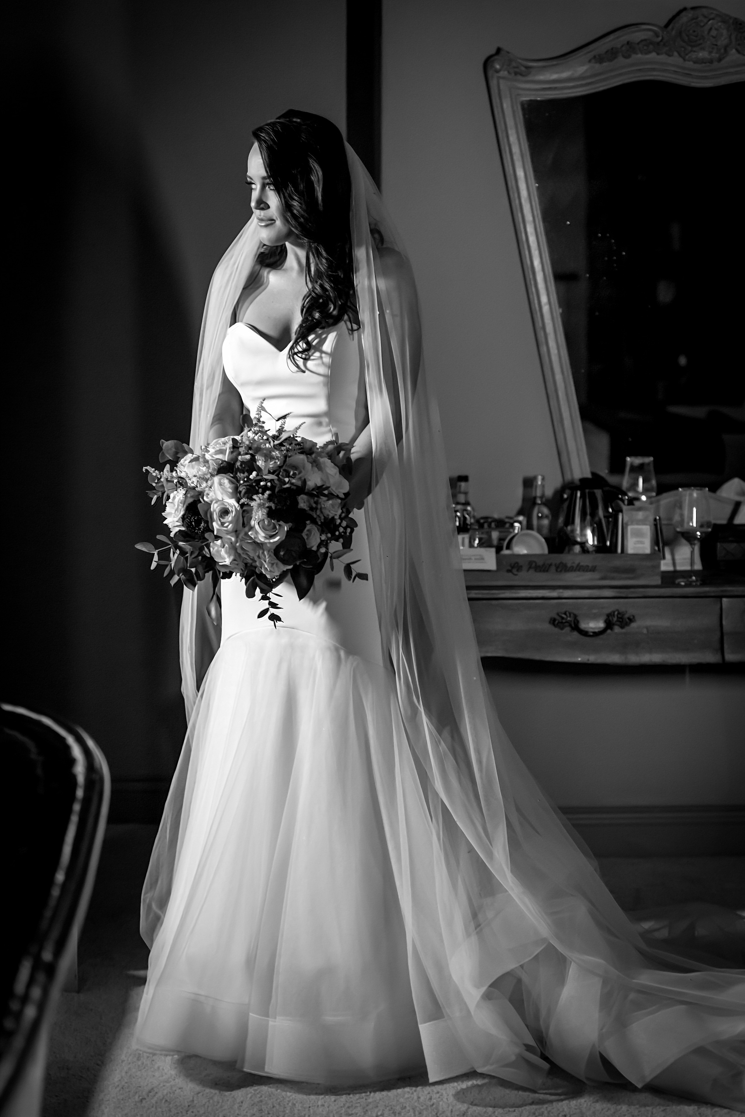 Black and white monochrome relaxed photograph of bride holding bouquet at Le Petit Chateau in Otterburn, Northumberland