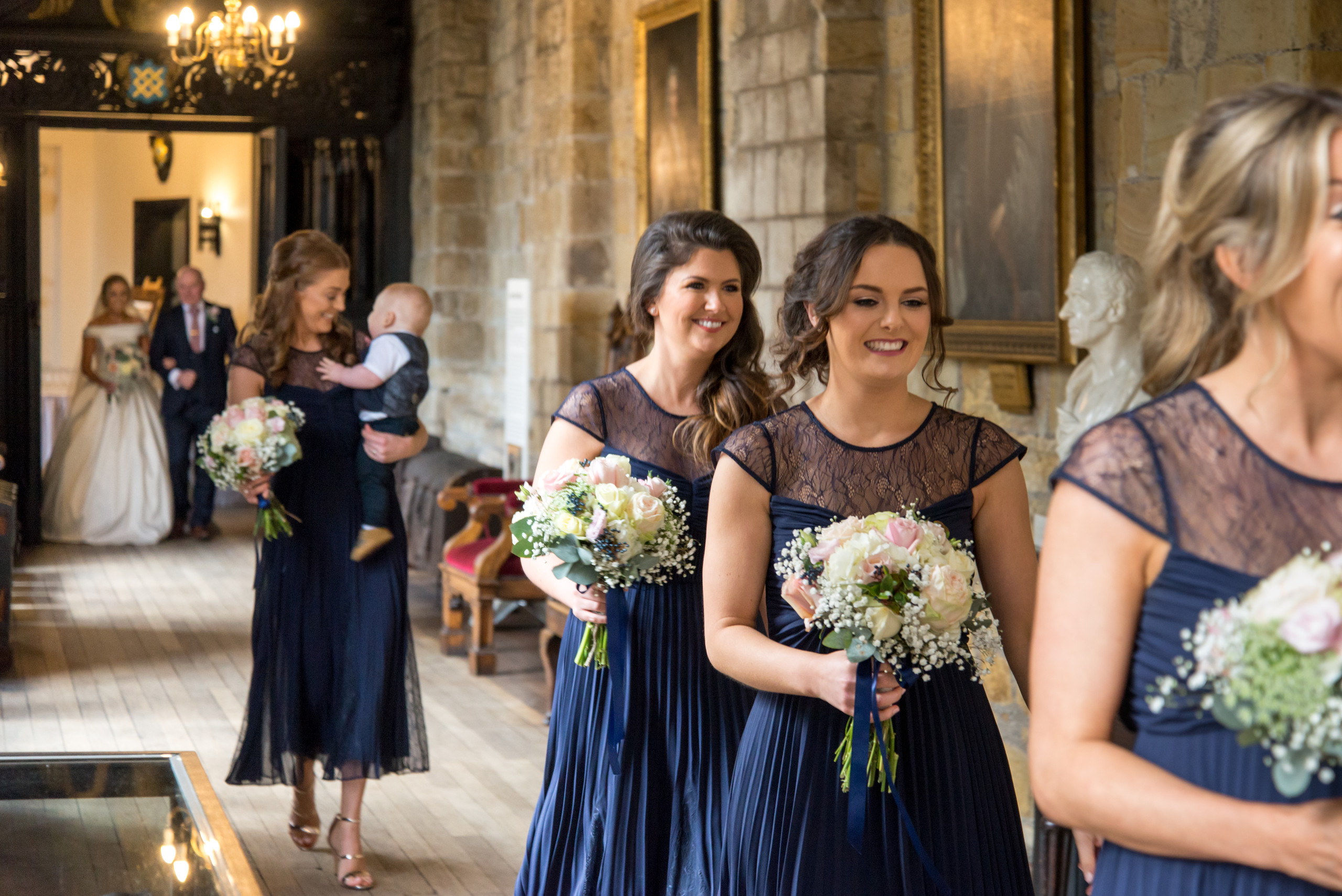 Photograph of bride and relaxed, smiling bridesmaids with bouquets in corridor of historic Tunstall Chapel of Durham Castle on day of wedding ceremony