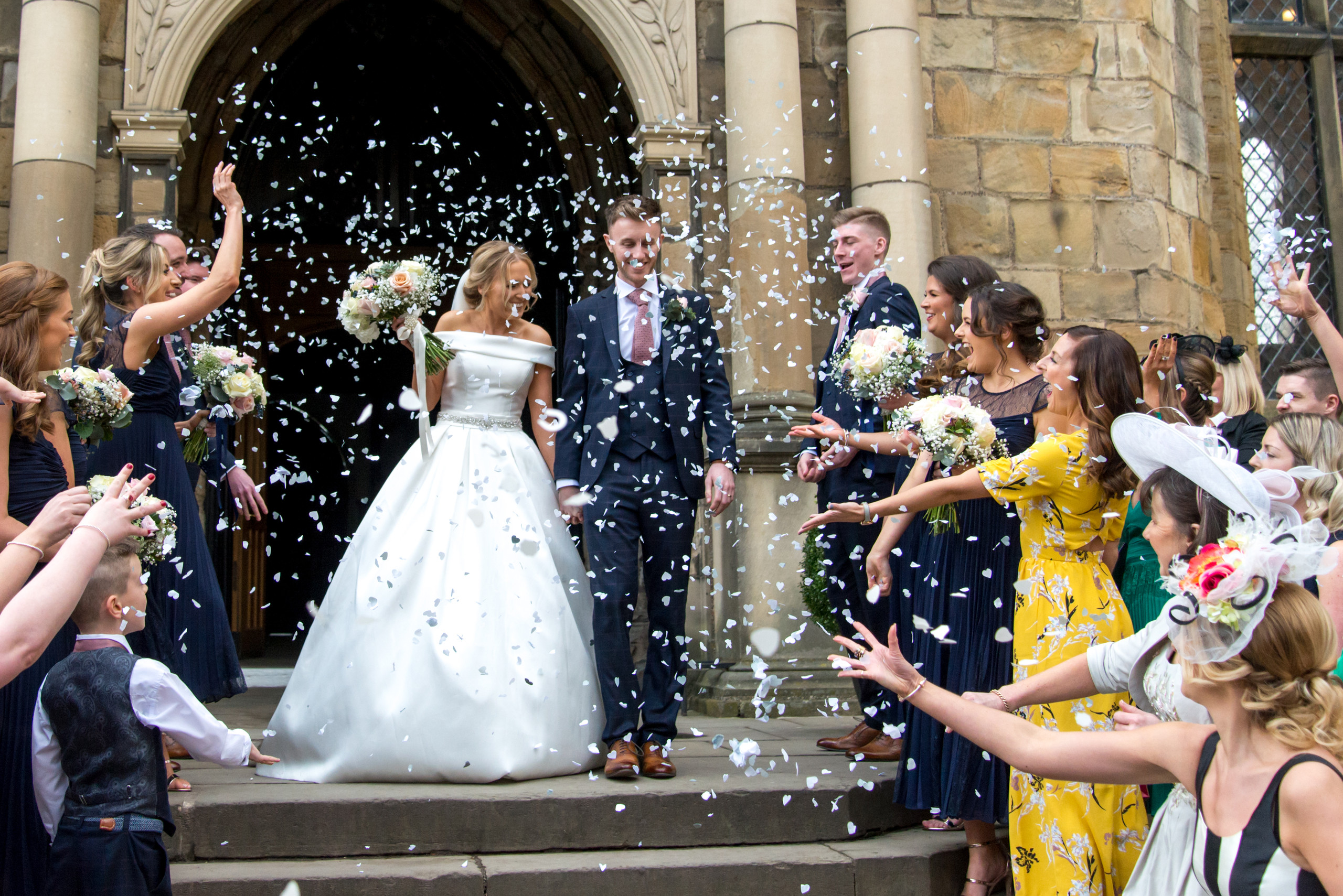Photography of confetti thrown at the bride and groom on the steps of the Bishops Hall in the Inner Bailey of Durham Castle on day of wedding ceremony