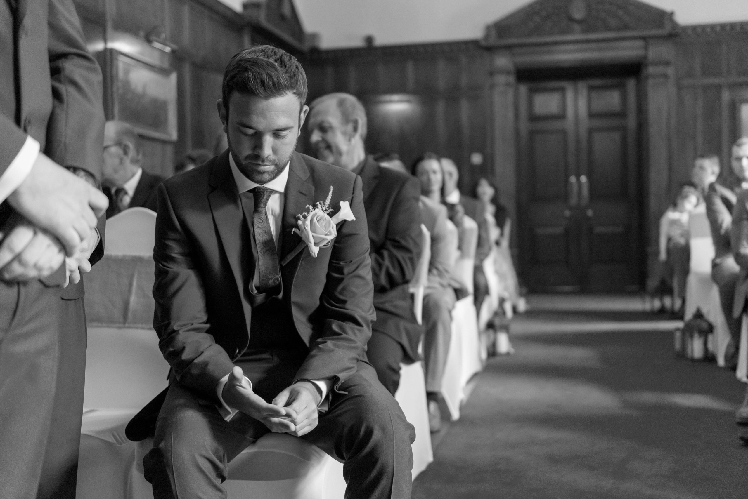 Candid black and white monochrome photograph of groom waiting nervously at aisle for bride on wedding day at Ellingham Hall wedding venue in Northumberland