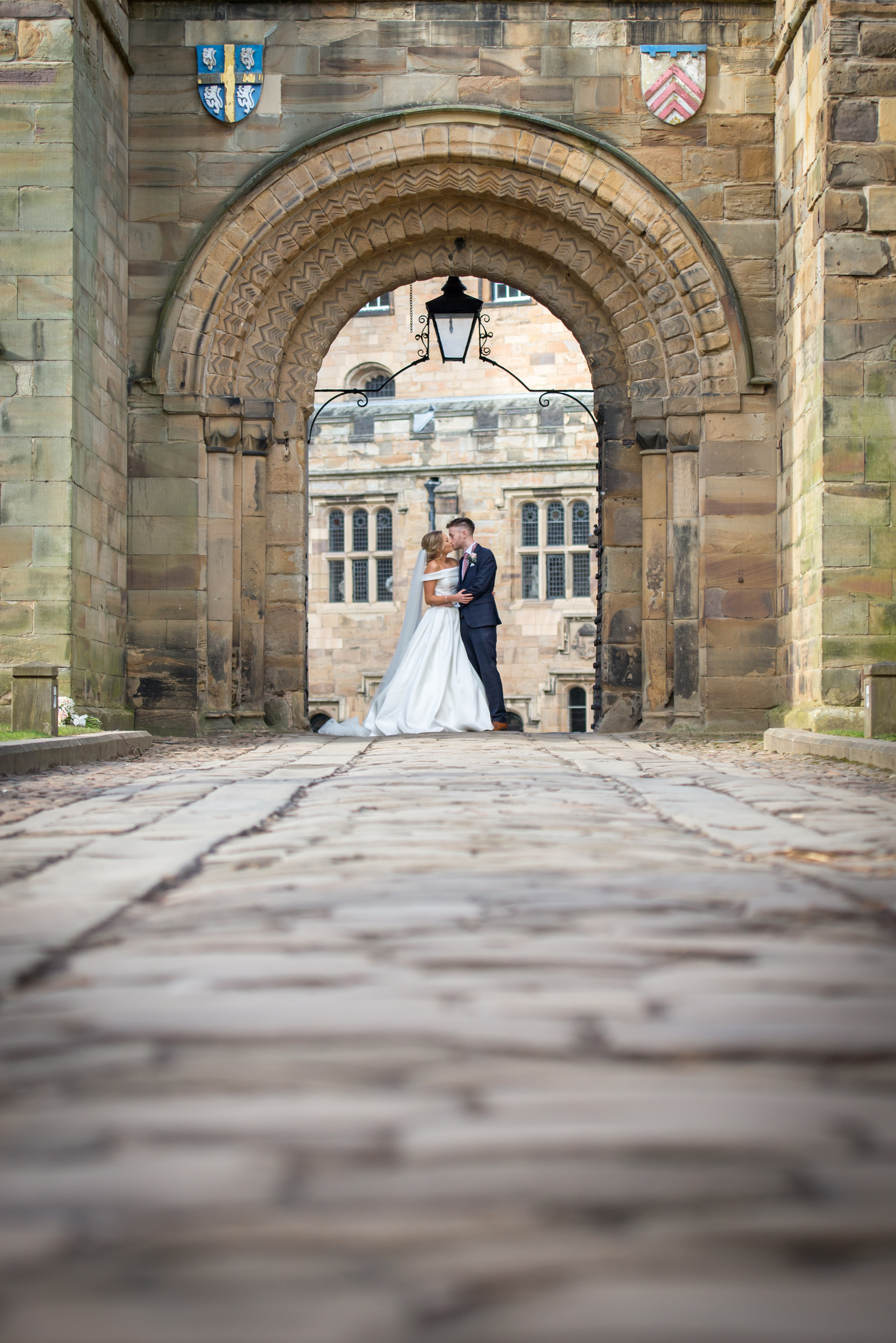 Relaxed wedding photography of bride and groom kissing in entrance archway to Inner Bailey of historic venue Durham Castle in Durham City