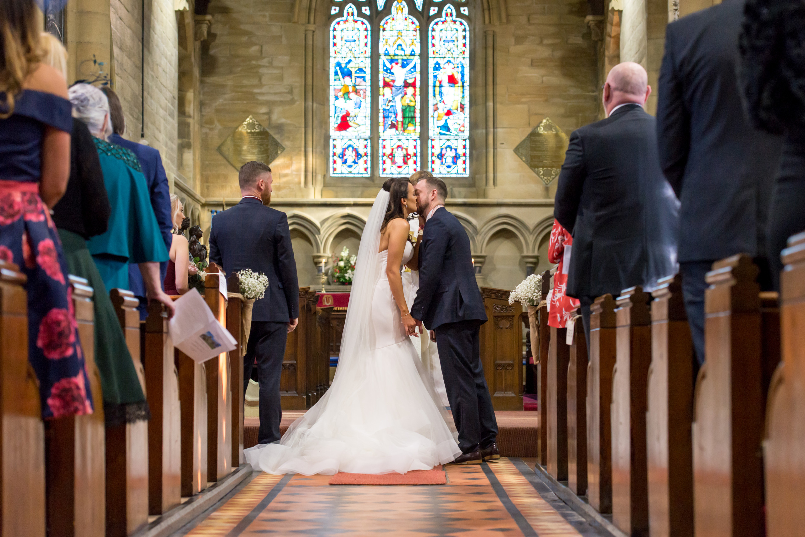 First kiss between husband and wife in church ceremony, photographed by Bride and Groom Wedding Photography in Northumberland church