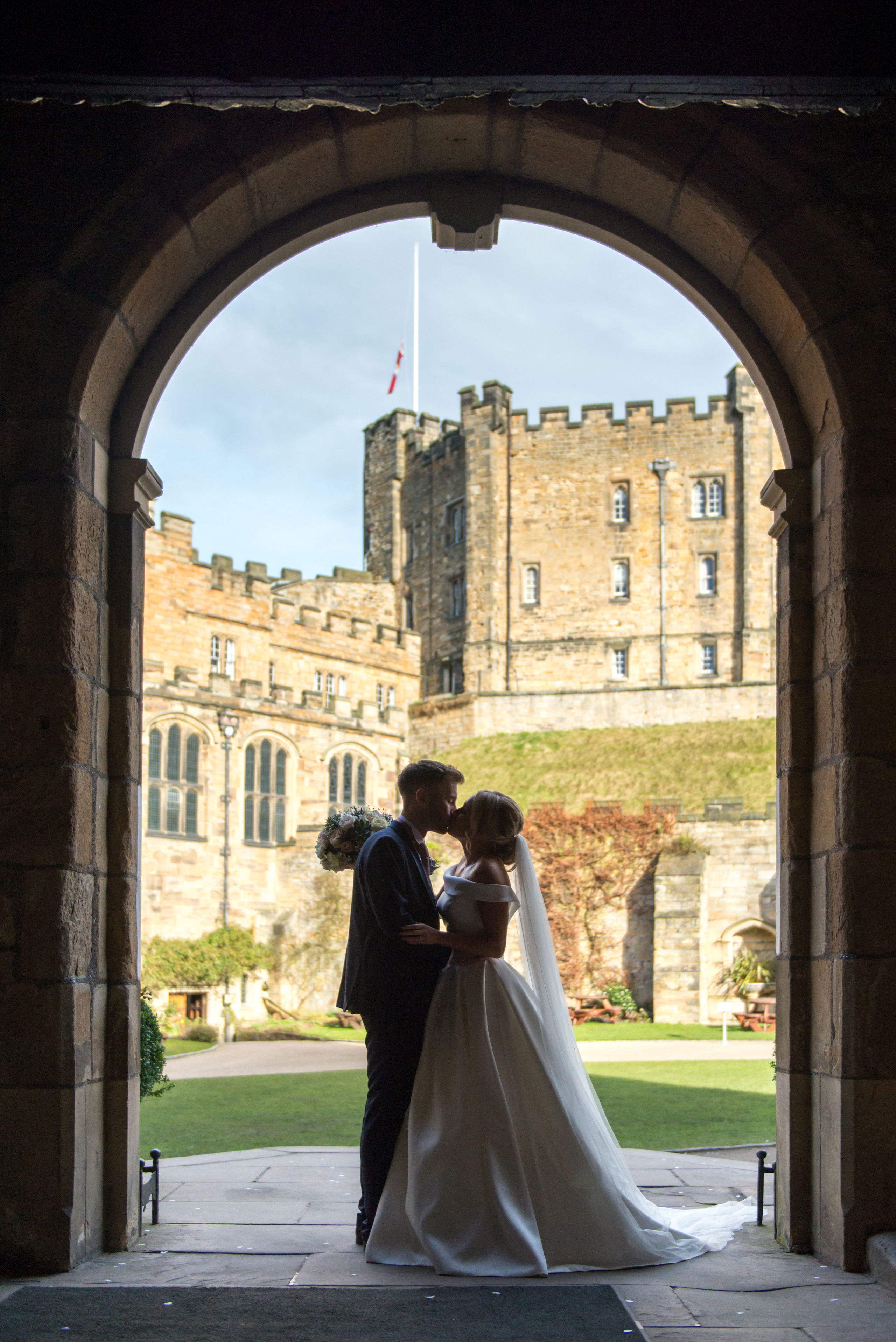 Relaxed wedding photography silhouette of bride and groom kissing in entrance archway to Bishops Hall near Inner Bailey of historic venue Durham Castle in Durham City