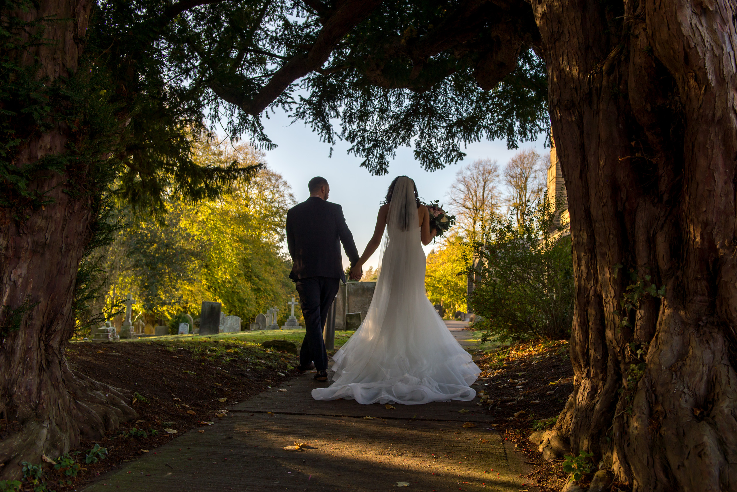 Photograph of relaxed bride and groom walking down pathway of church after wedding day ceremony
