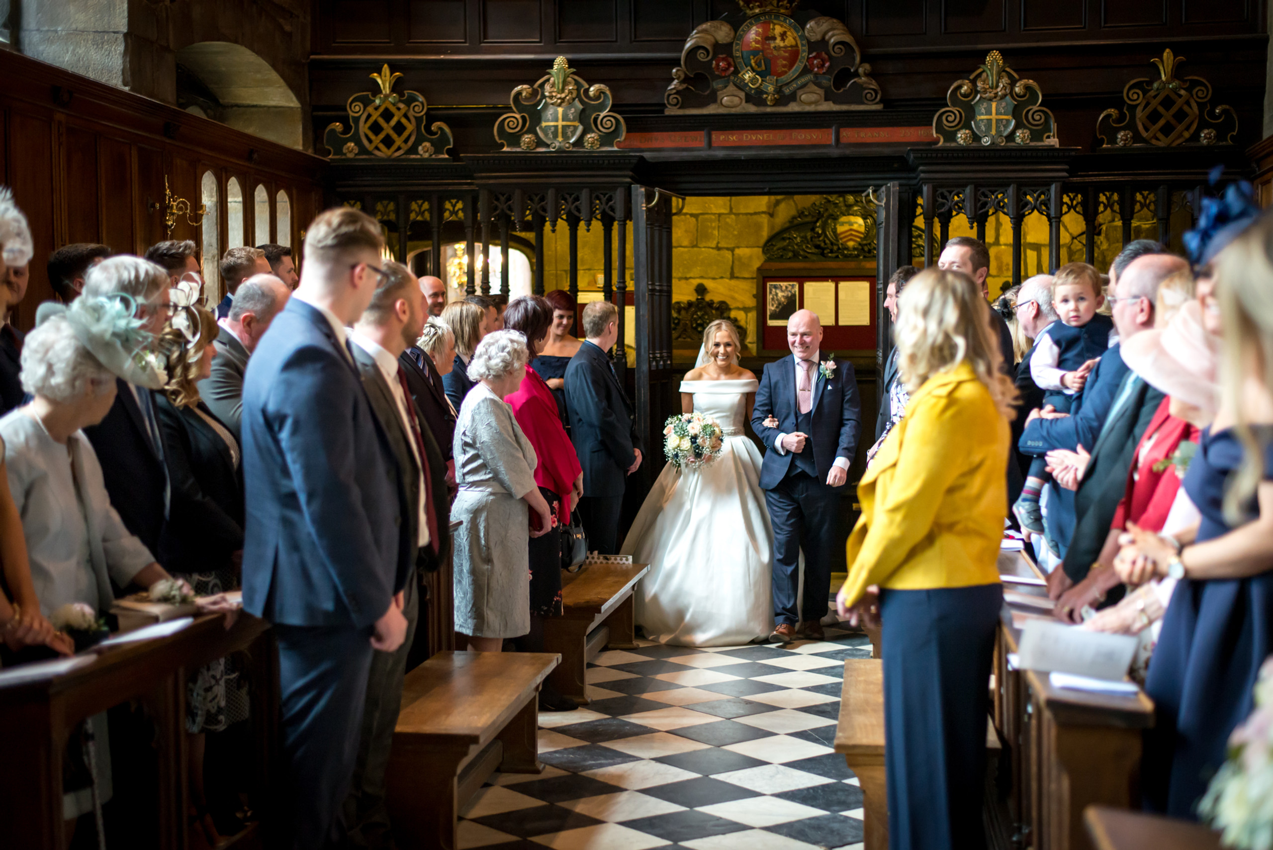 Photograph of relaxed, smiling bride with father walking down the aisle in historic Tunstall Chapel of Durham Castle on day of wedding ceremony