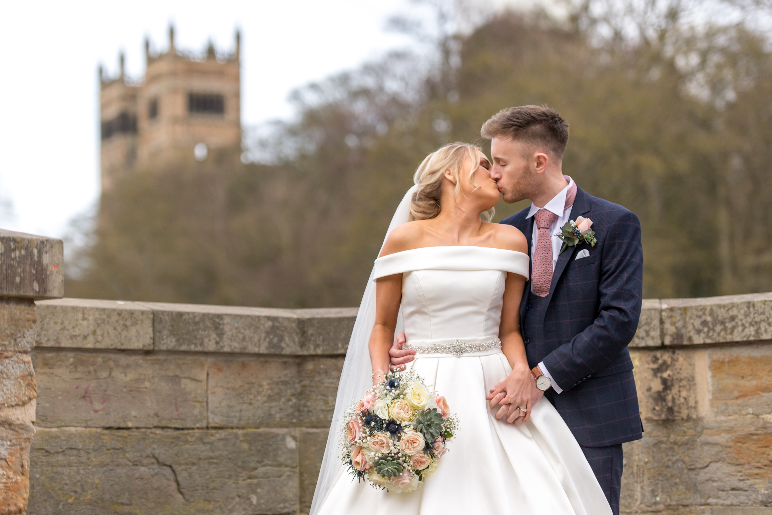 Wedding photography of bride and groom kiss on wedding day on Prebends Bridge in Durham with Durham Cathedral in background