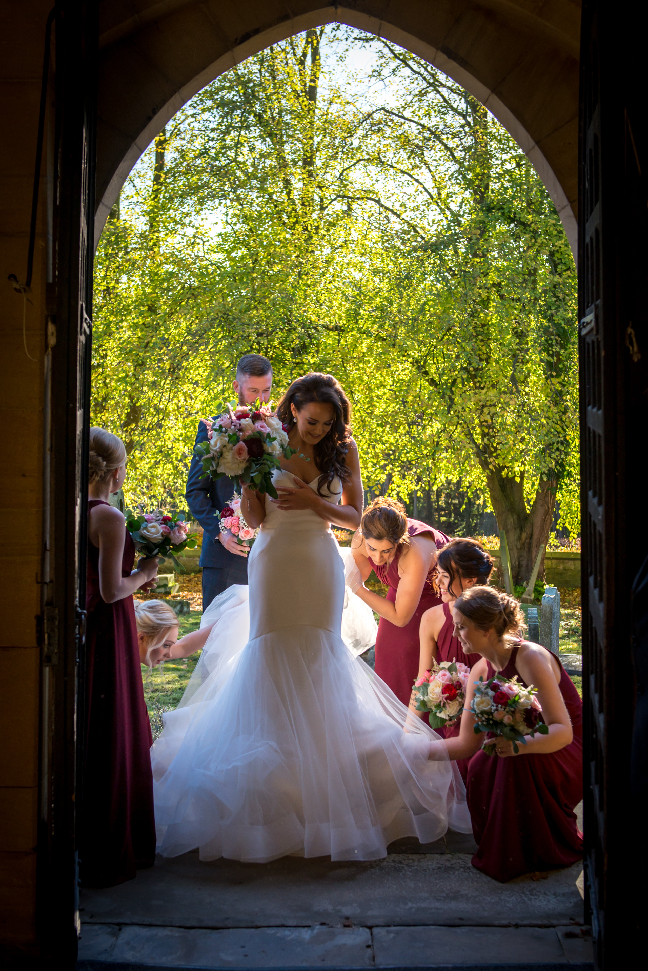 Final preparations before the bride's church ceremony entrance with bridesmaids adjusting the wedding dress