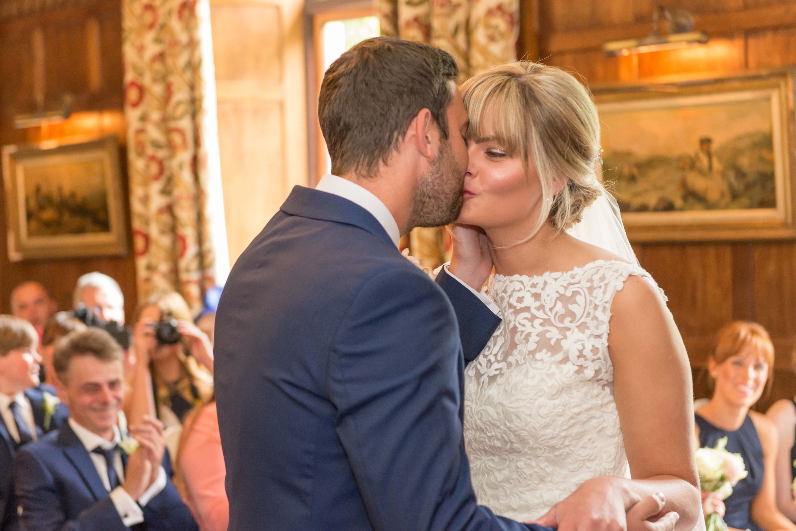 Photograph of bride and groom's first kiss during wedding ceremony on wedding day at Ellingham Hall wedding venue in Northumberland