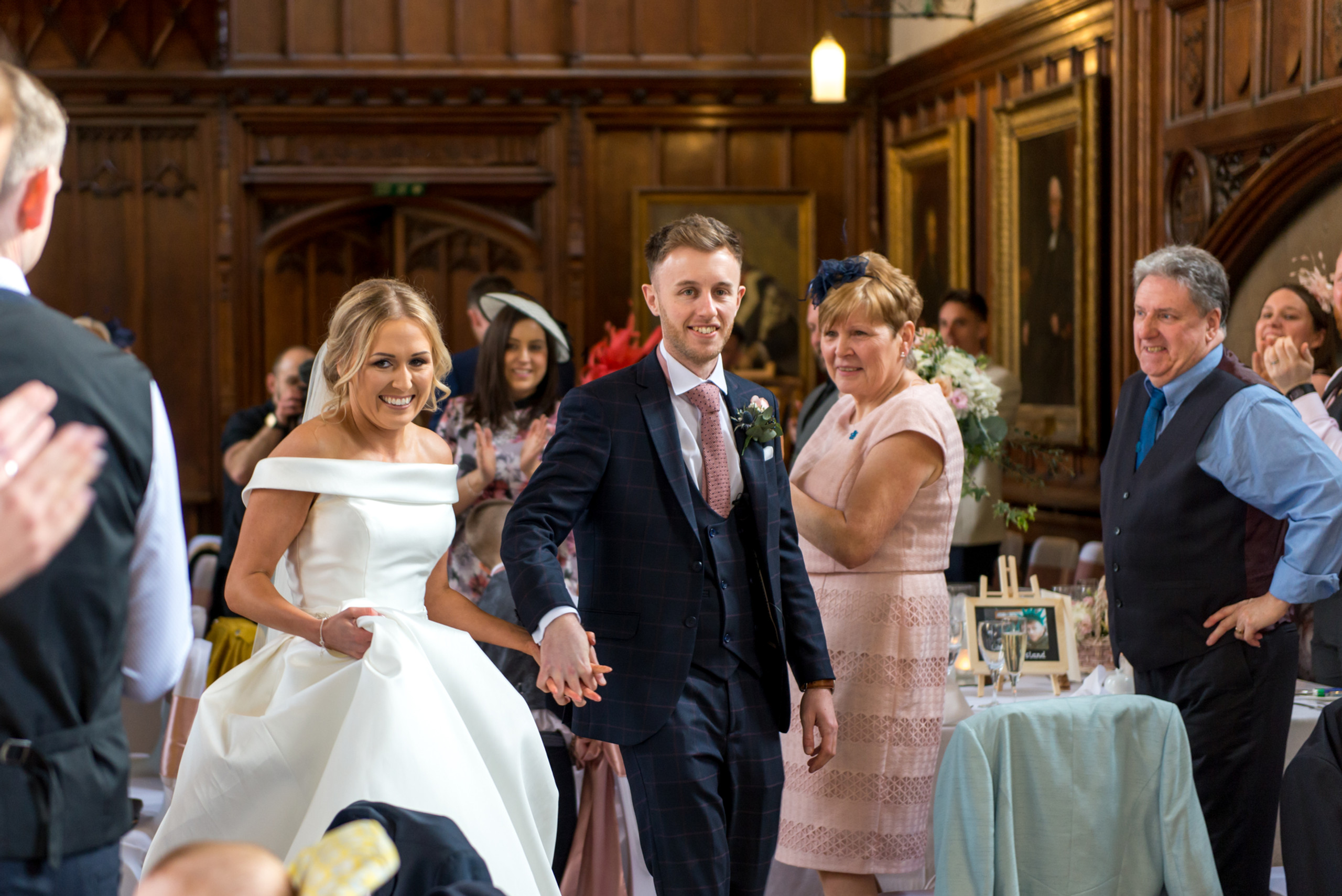 Relaxed wedding photography of bride and groom smiling as they enter Bishops Hall for wedding breakfast at historic venue Durham Castle in Durham City