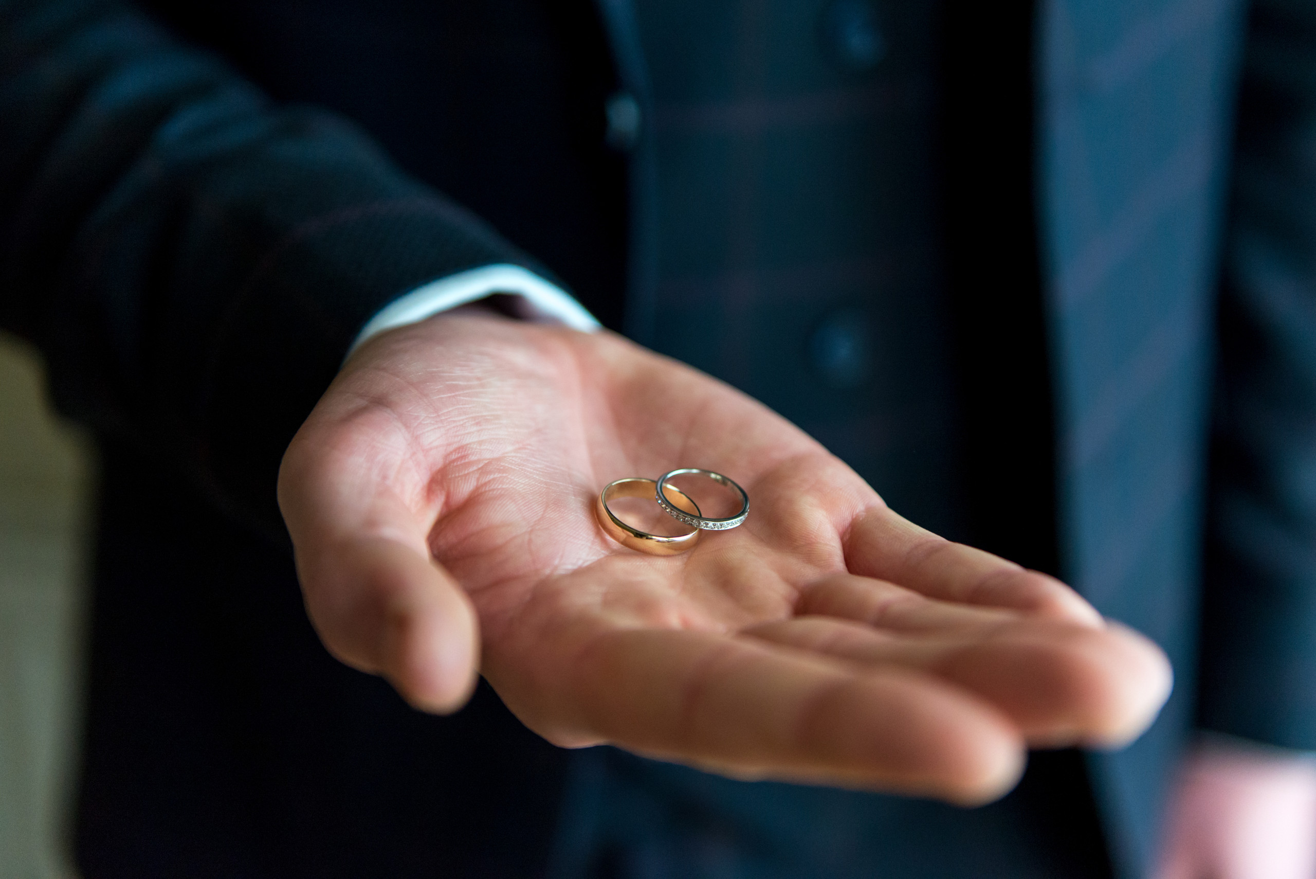 Best man holding bride and groom wedding rings in palm of hand on wedding day