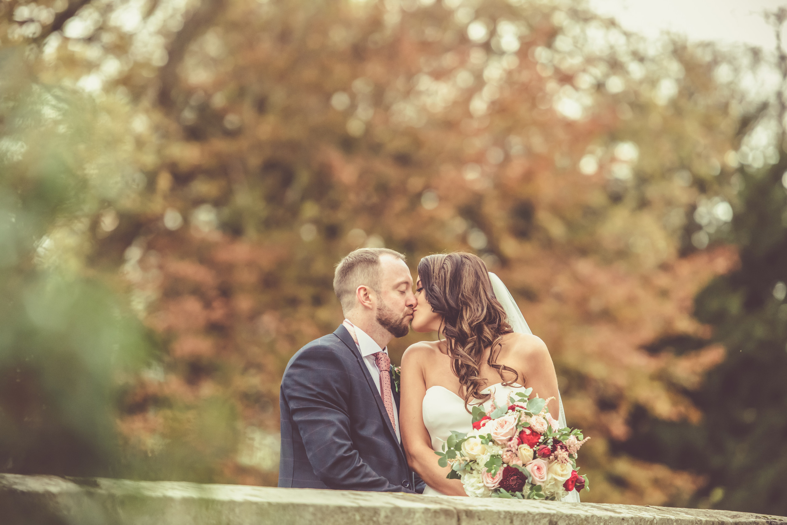 Relaxed candid photograph of bride and groom kissing on autumn wedding day at Le Petit Chateau in Otterburn, Northumberland