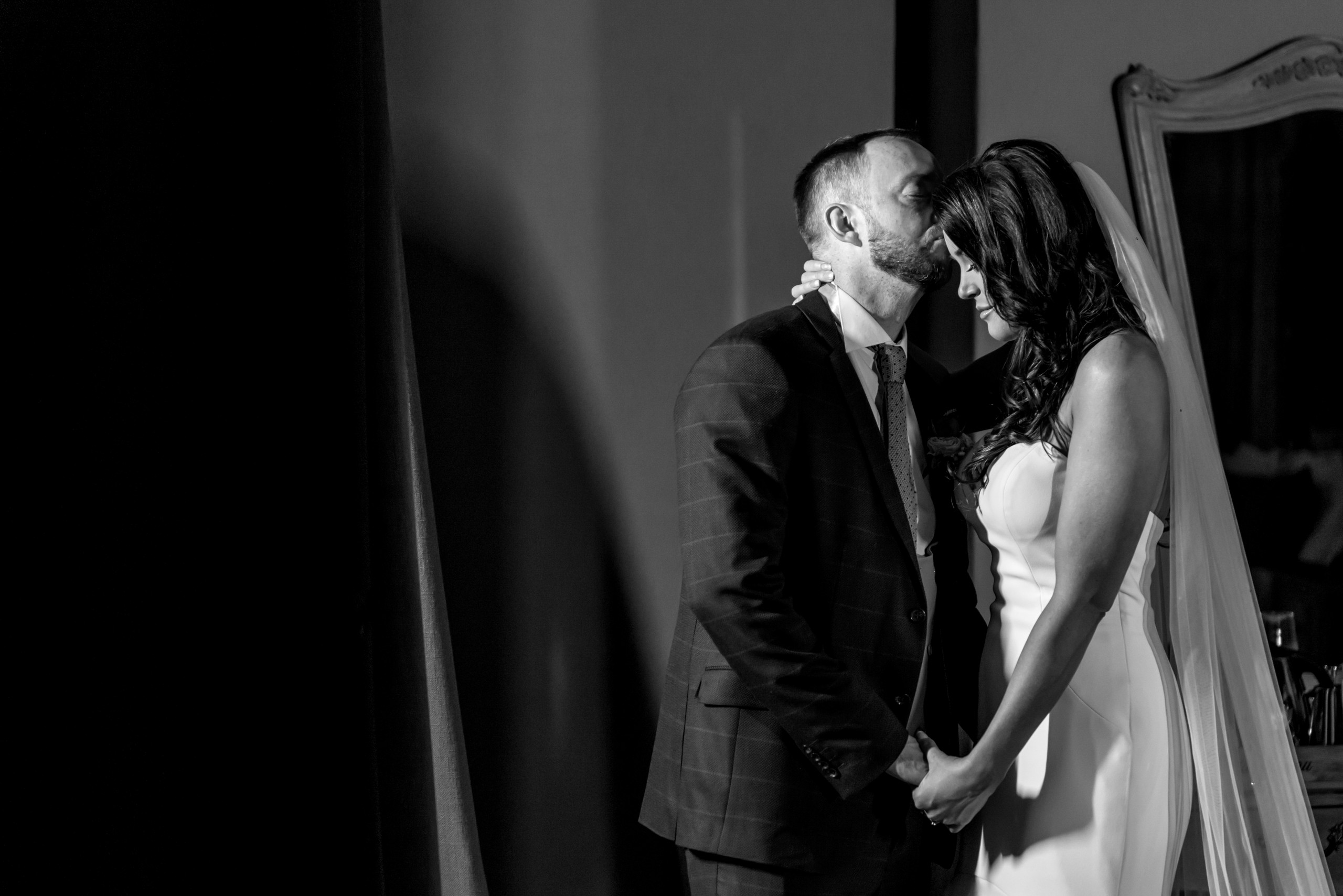 Black and white monochrome photograph of stunning bride and groom kissing at Le Petit Chateau in Otterburn, Northumberland
