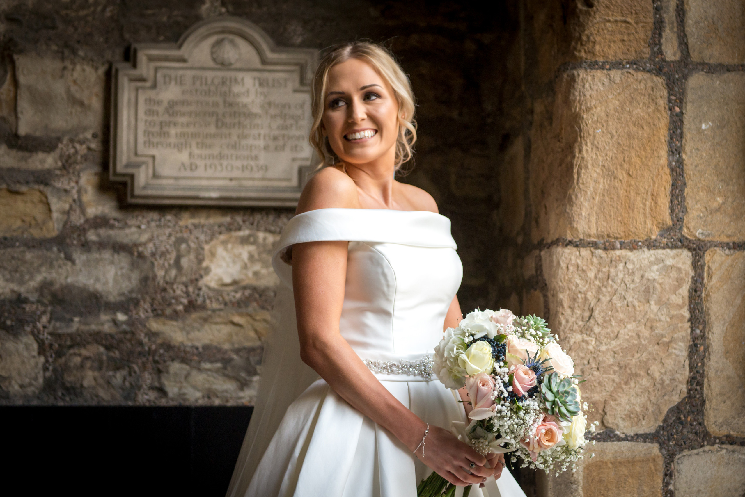 Relaxed wedding photography of bride holding bouquet smiling in entrance archway between Bishops Hall and Inner Bailey of historic venue Durham Castle in Durham City