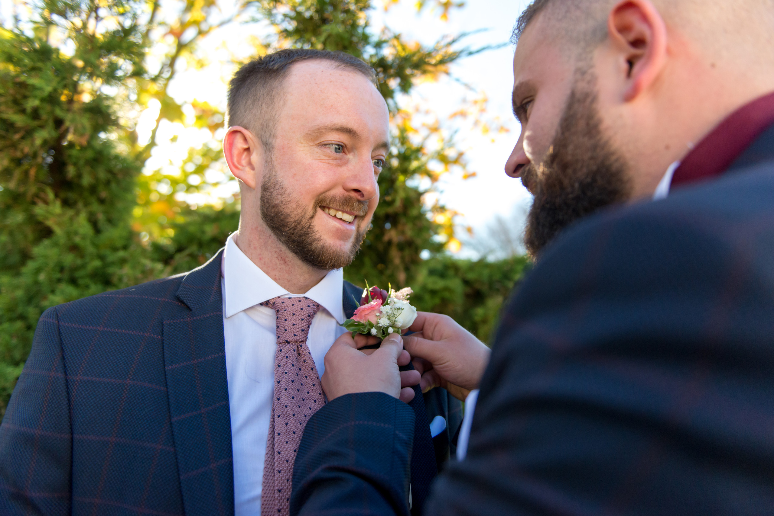 Groom in navy suit with best man putting on buttonhole flowers