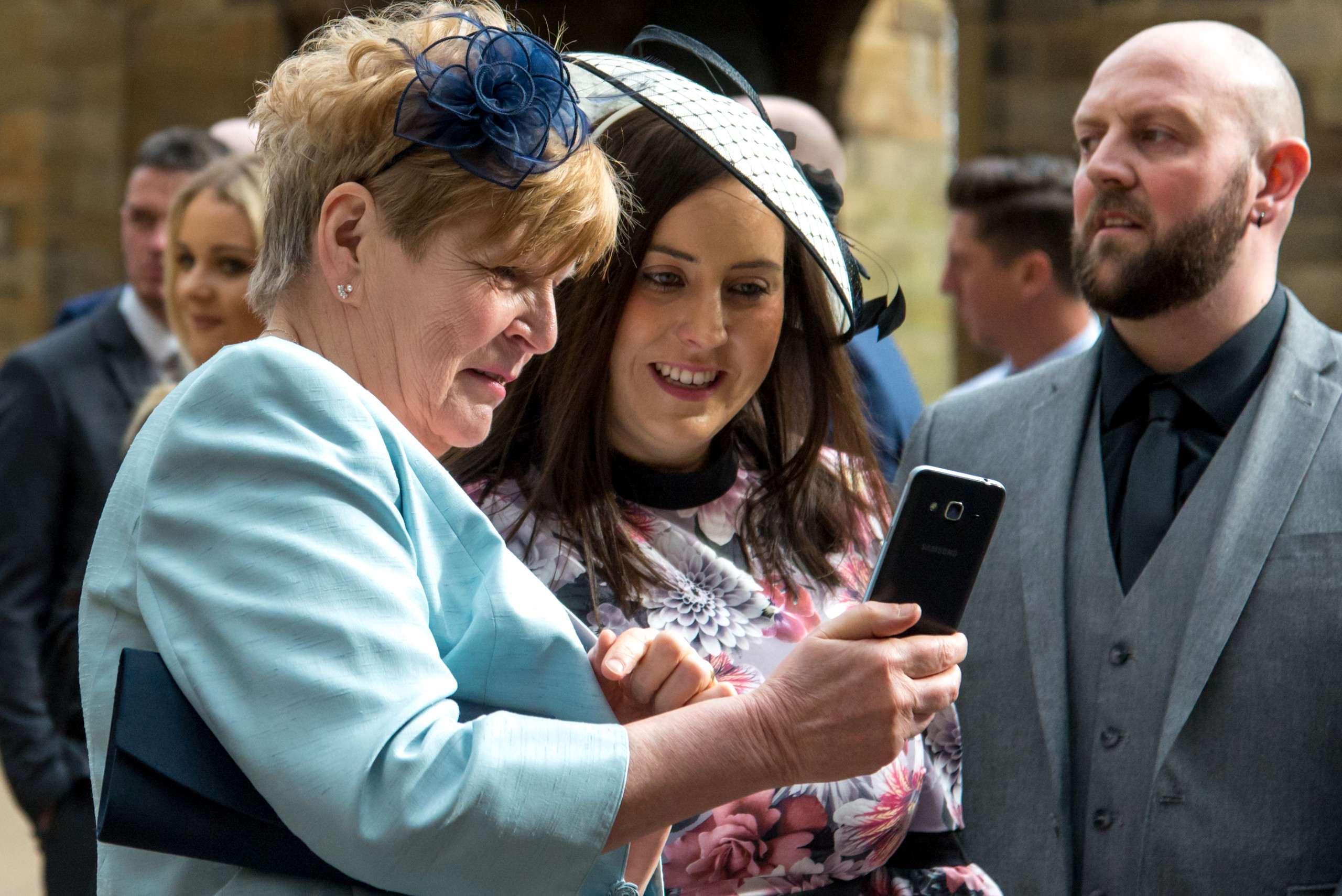 Candid photograph of guests looking at wedding photography on mobile phone on wedding day