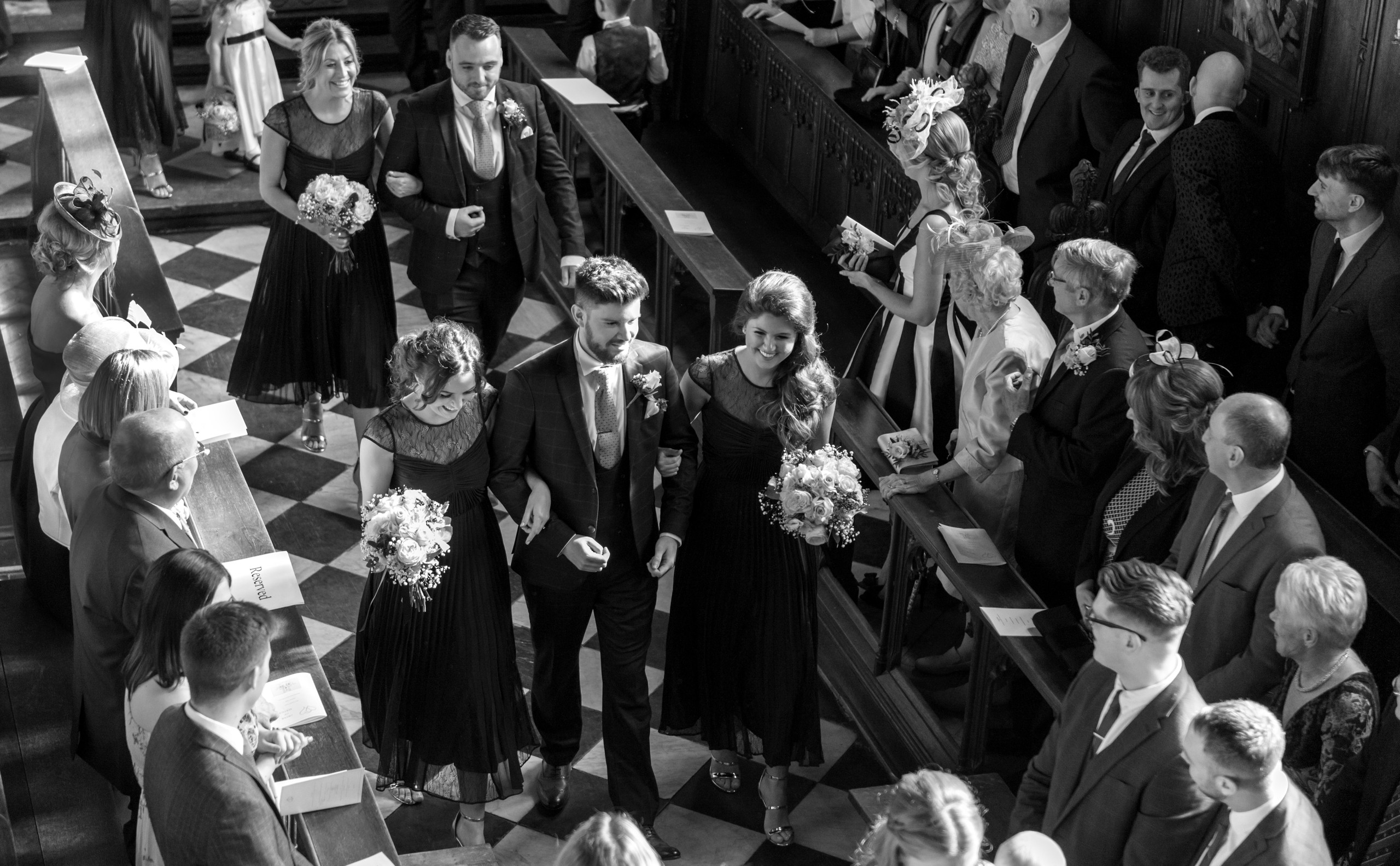 Relaxed black and white monochrome photograph of bridesmaids and groomsman walking down the aisle of Tunstall Chapel of Durham Castle on day of wedding ceremony