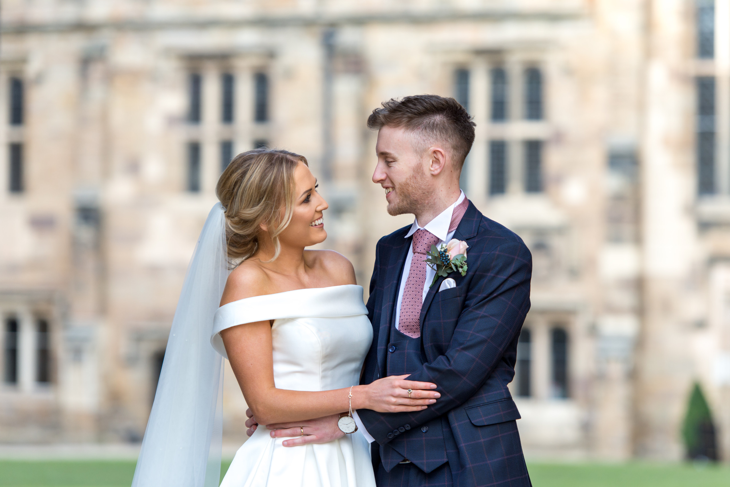 Relaxed wedding photography of bride and groom smiling in Inner Bailey of historic venue Durham Castle in Durham City