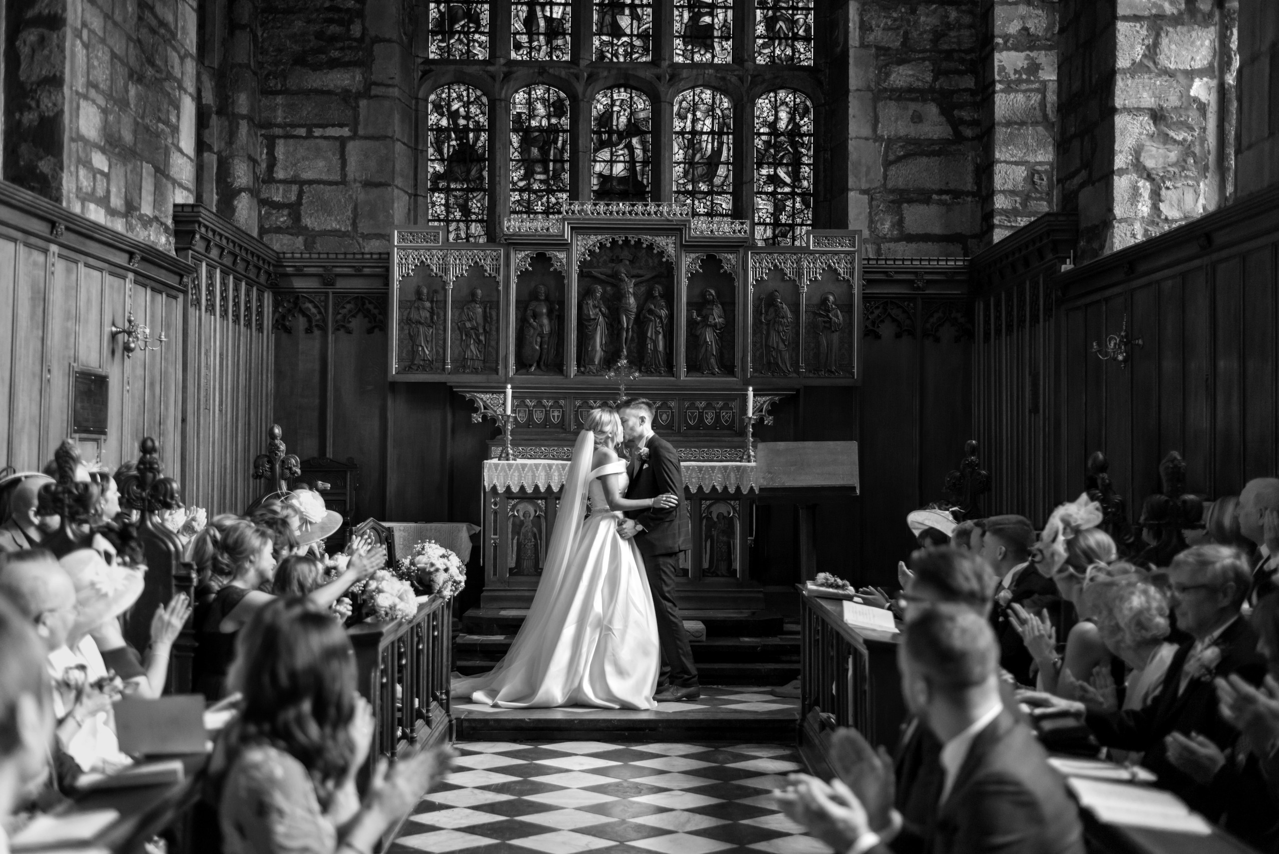 Black and white monochrome photograph of first kiss of bride and groom at the altar of Tunstall Chapel of Durham Castle on day of wedding ceremony