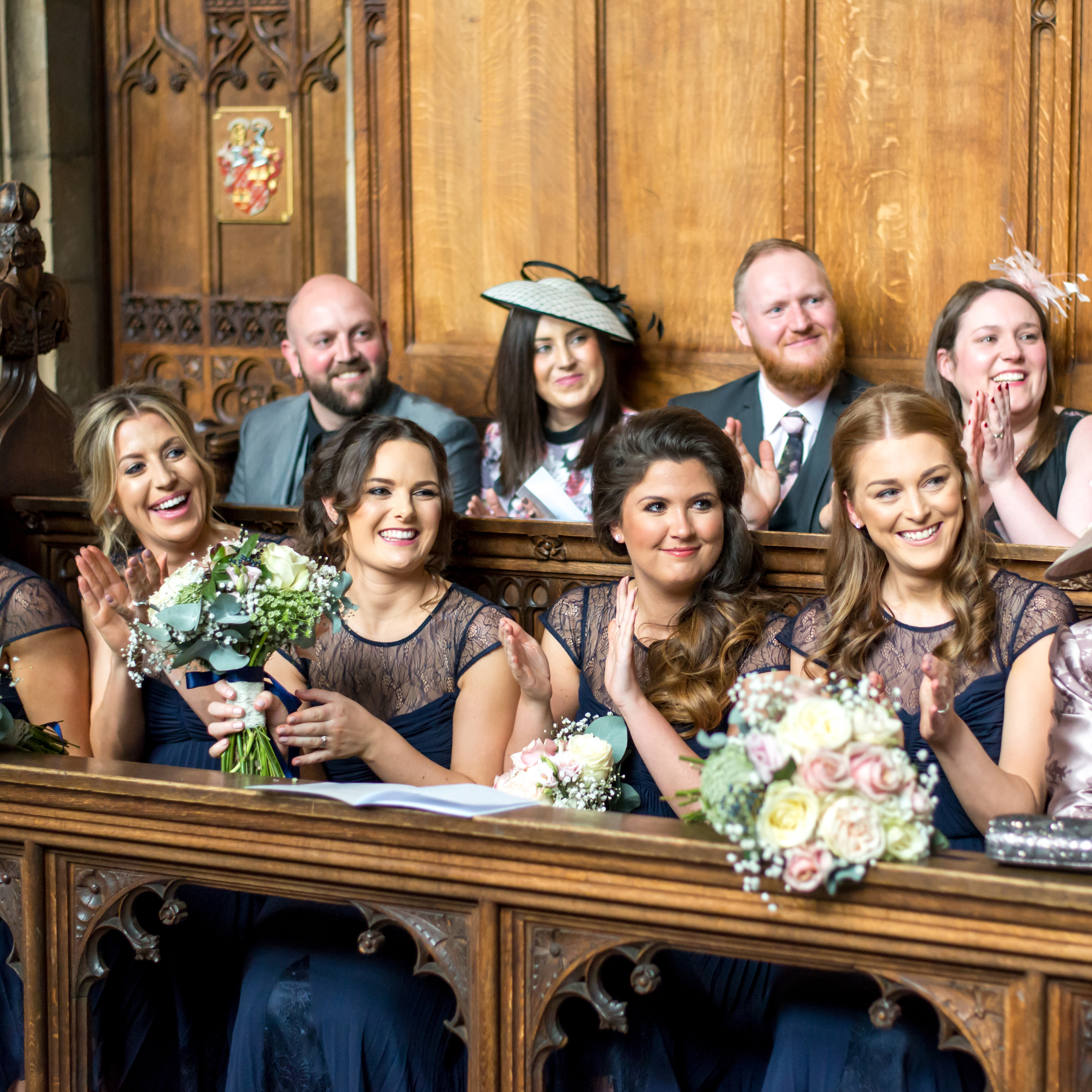 Photograph of bridesmaids and guests smiling and clapping the bride and groom at the end of the wedding ceremony in the Tunstall Chapel of Durham Castle on day of wedding ceremony