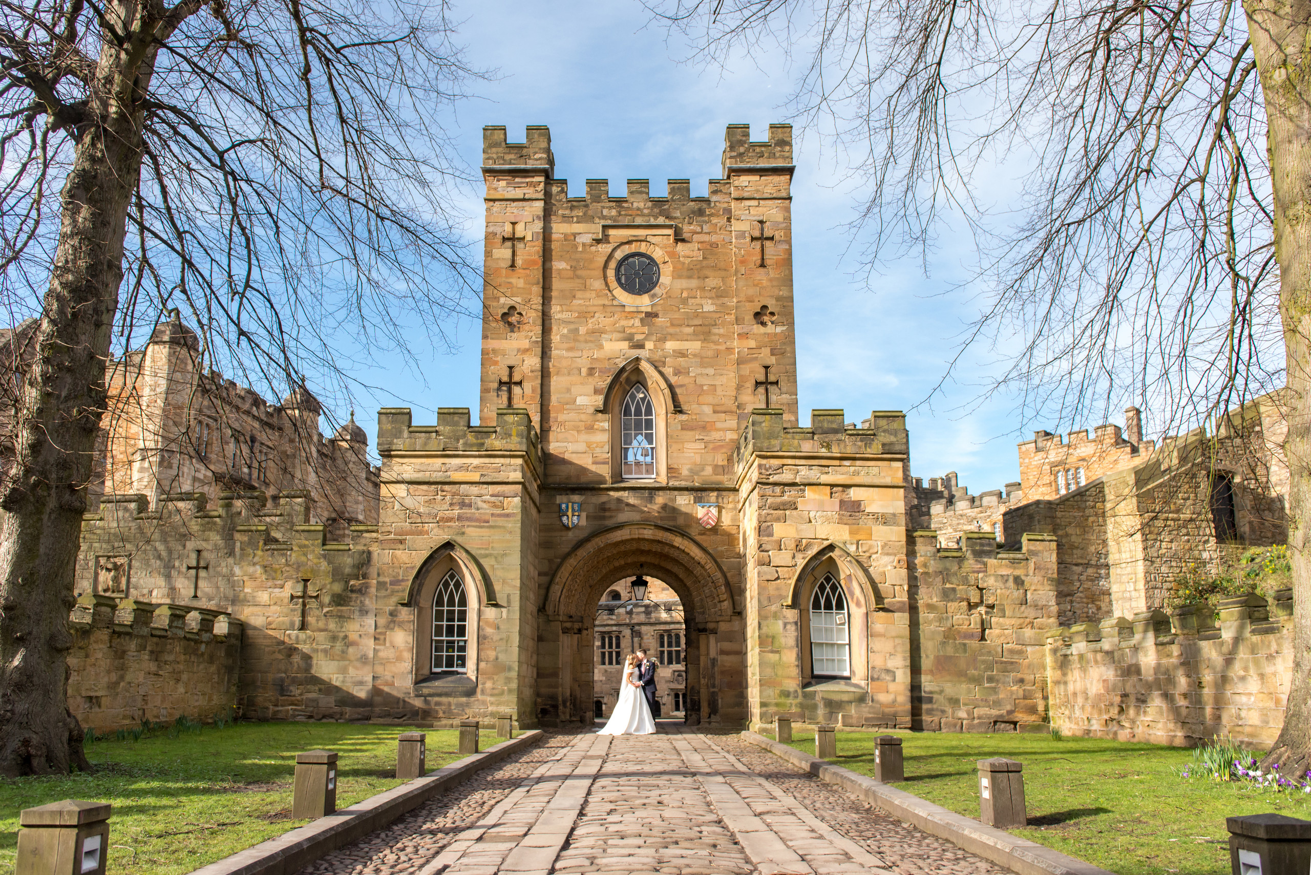 Photography of bride and groom on pathway entrance to gateway and Inner Bailey of historic venue Durham Castle in Durham City