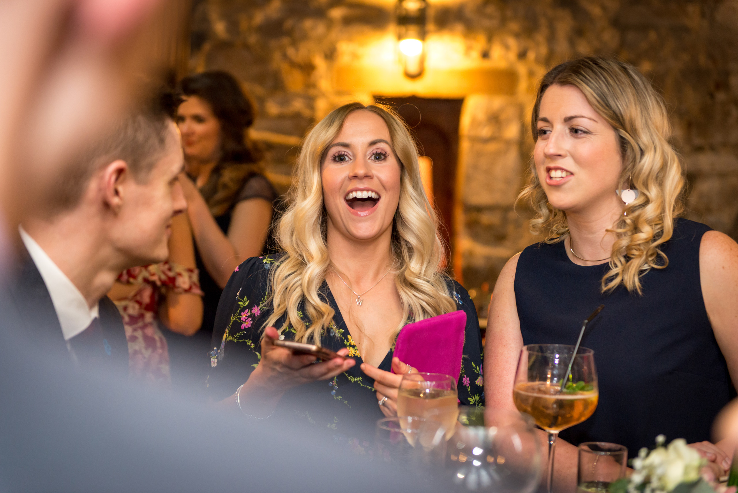 Candid photograph of guests in bar on wedding day at Durham Castle