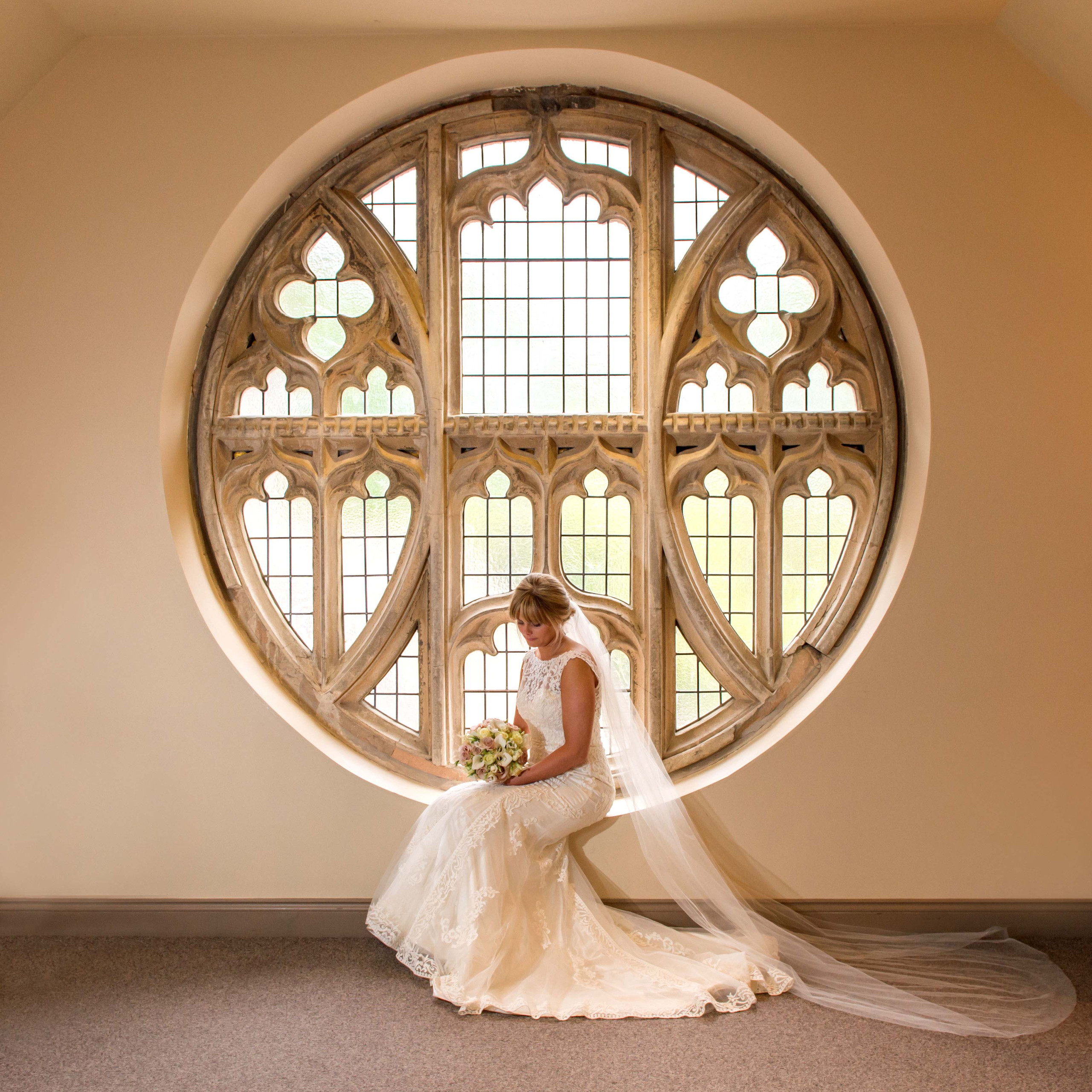 Stunning photograph of bride holding bouquet sat at circular round window at Ellingham Hall wedding venue in Northumberland