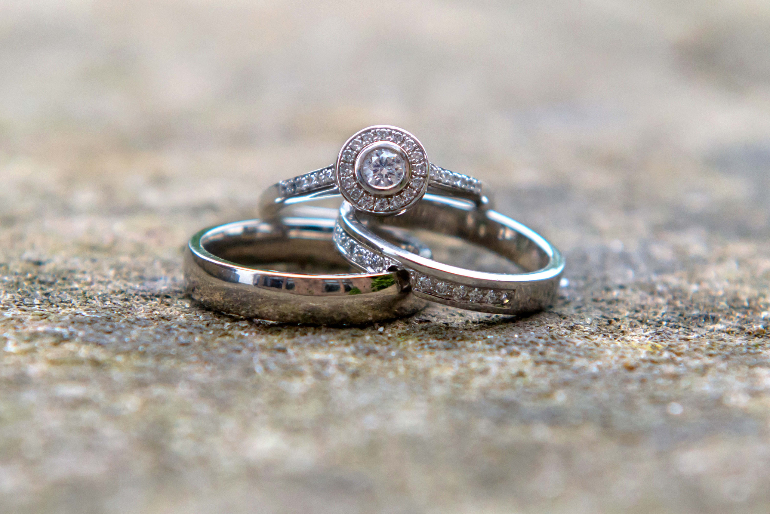 Close up photograph of platinum and diamond bride and groom wedding rings with engagement ring on wedding day