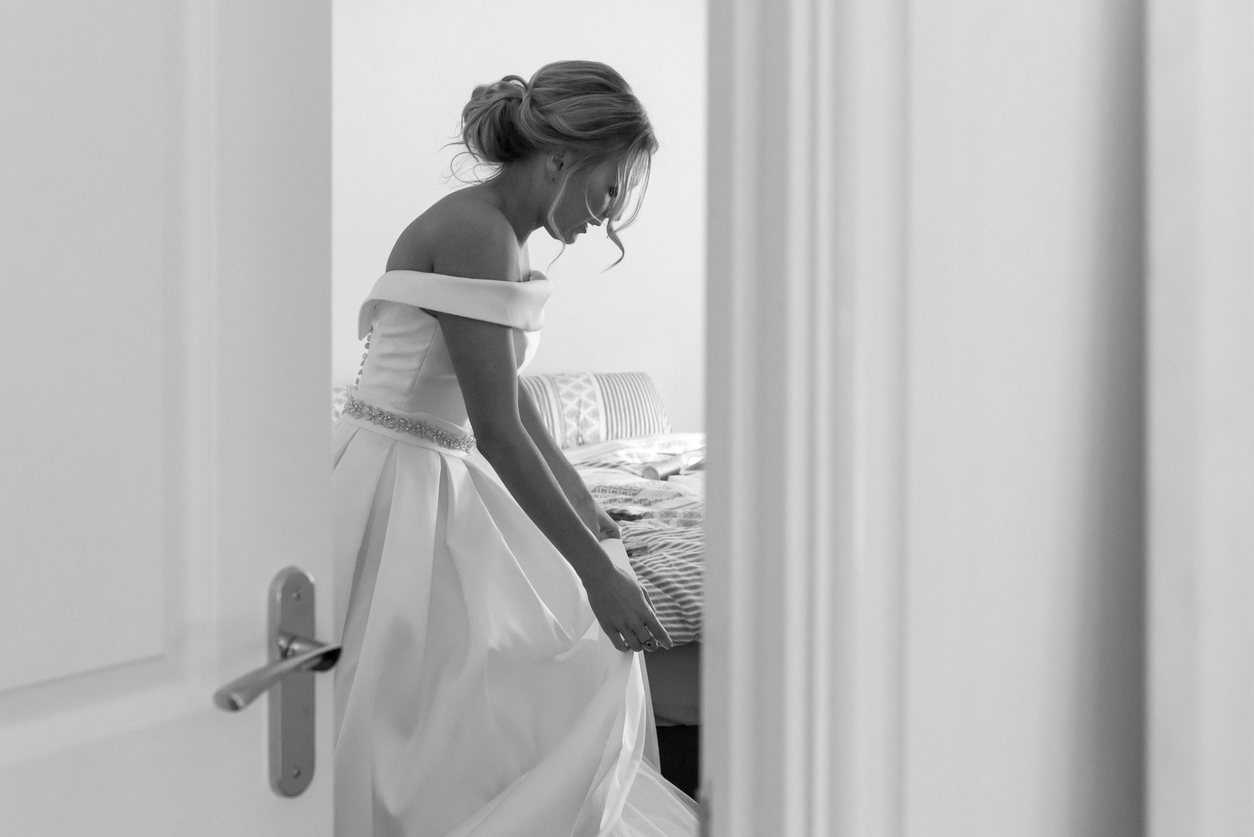 Black and white monochrome image of bride putting on wedding dress in bedroom during bridal preparations on morning of wedding day