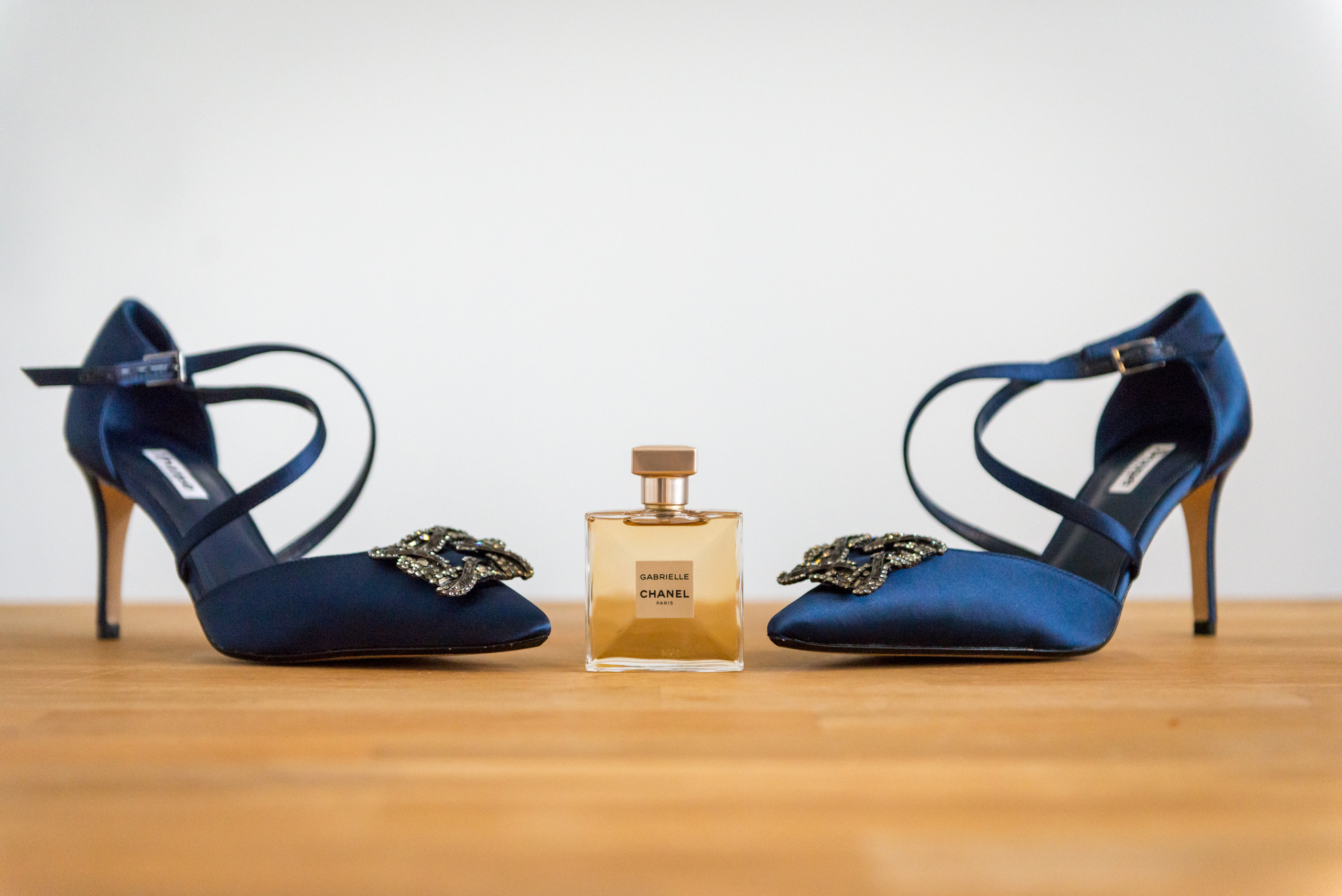 Photograph of Chanel Gabrielle perfume bottle and bride's blue high heel shoes on wedding day