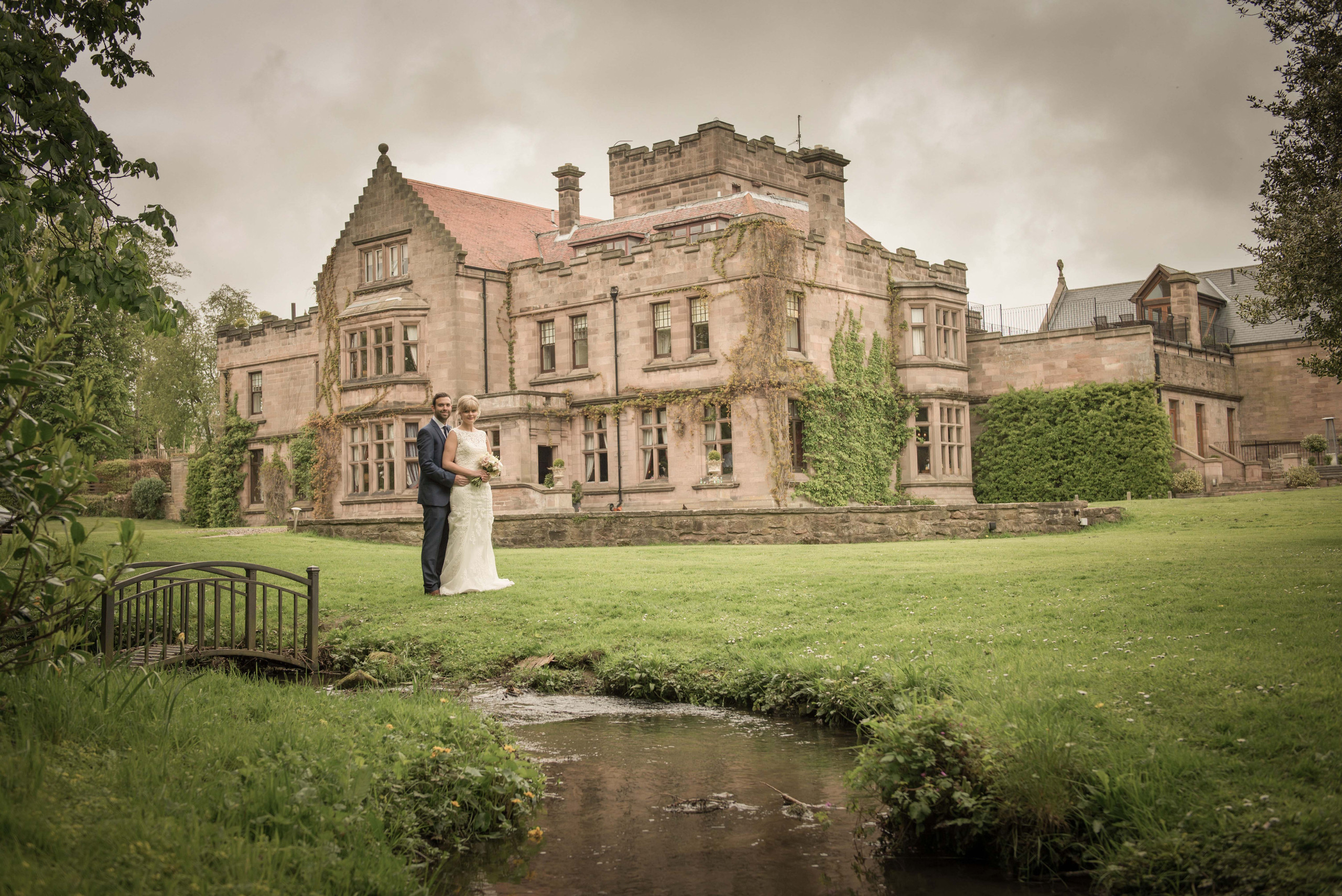 Posed photograph of bride and groom in grounds of Ellingham Hall wedding venue in Northumberland