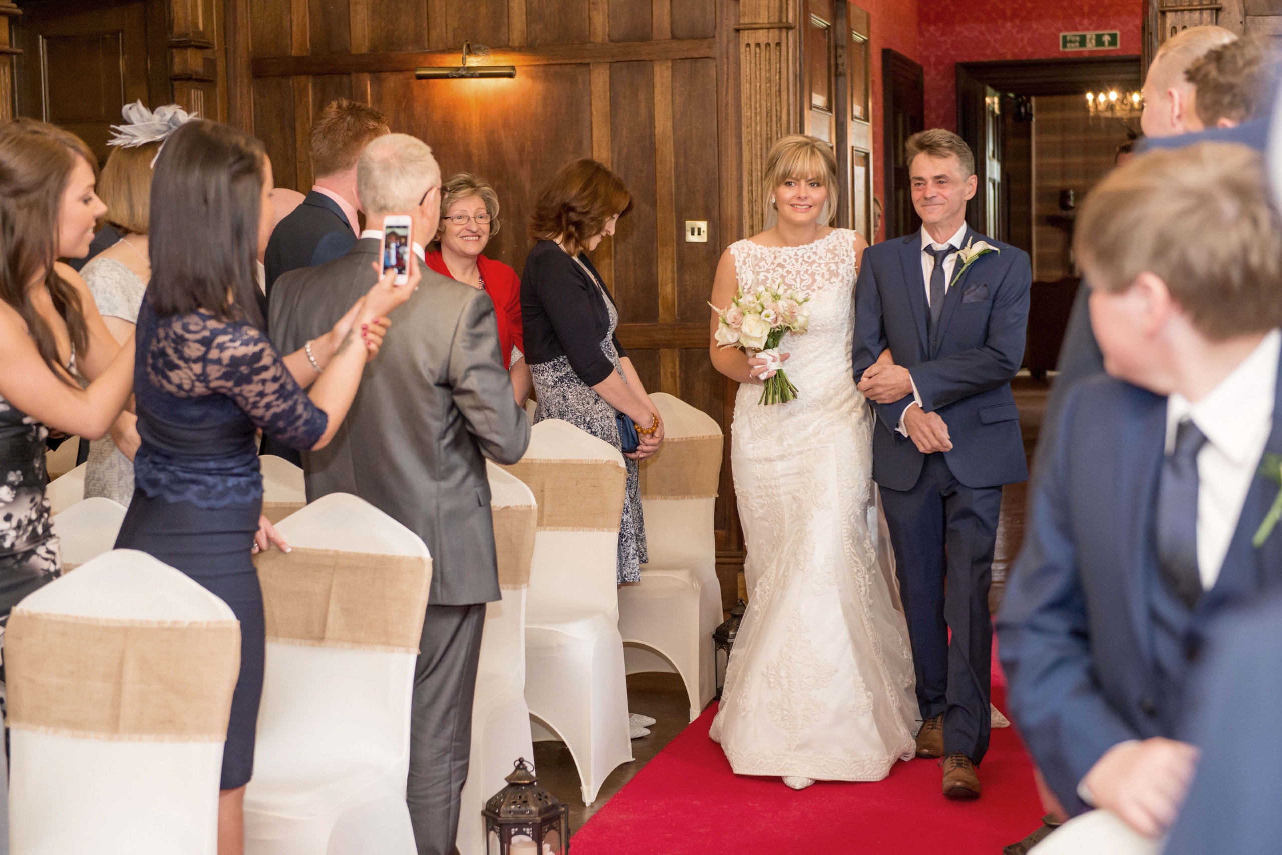 Photograph of bride walking down aisle on wedding day at Ellingham Hall wedding venue in Northumberland