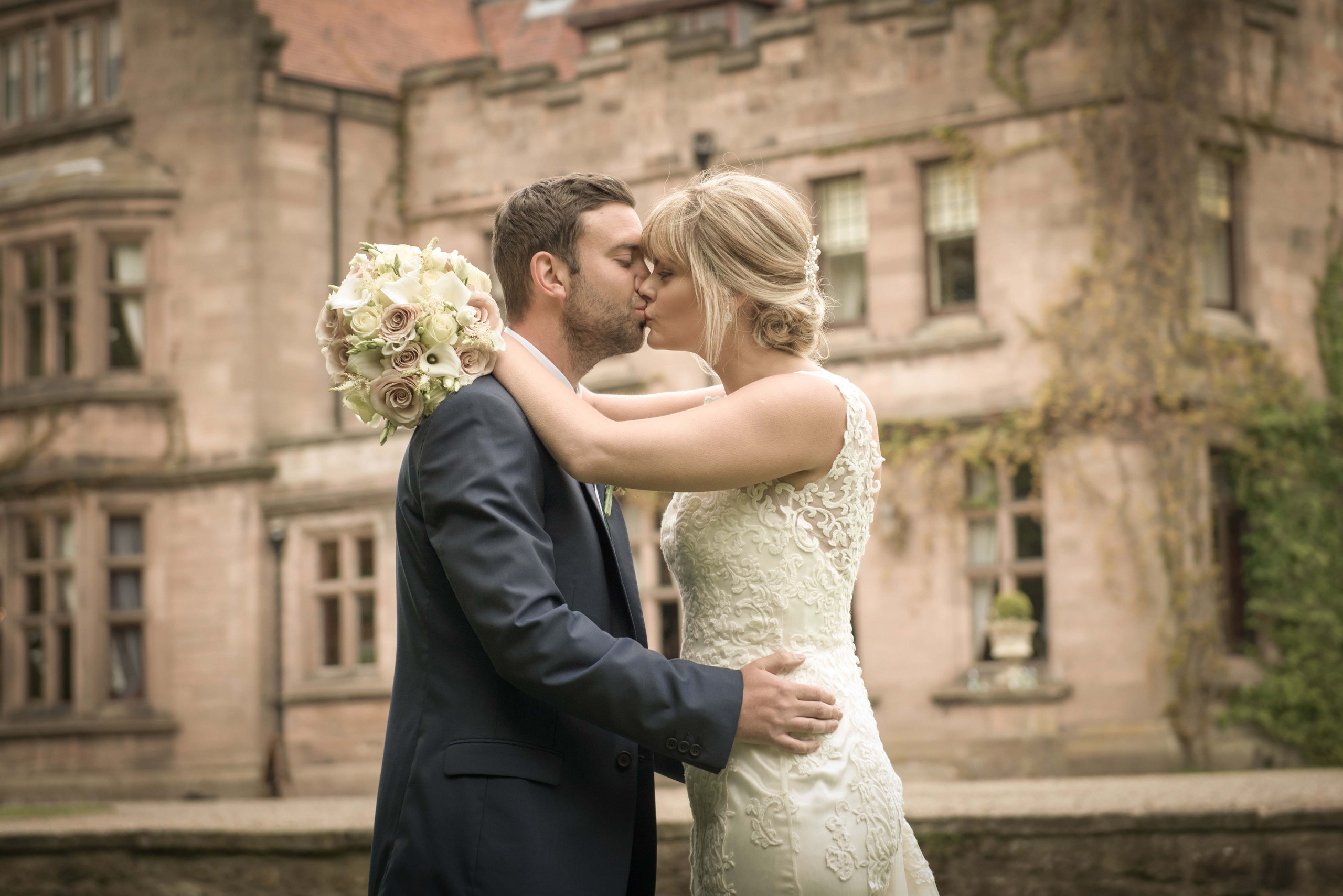 Posed photograph of bride and groom kissing in grounds of Ellingham Hall on wedding day in Northumberland