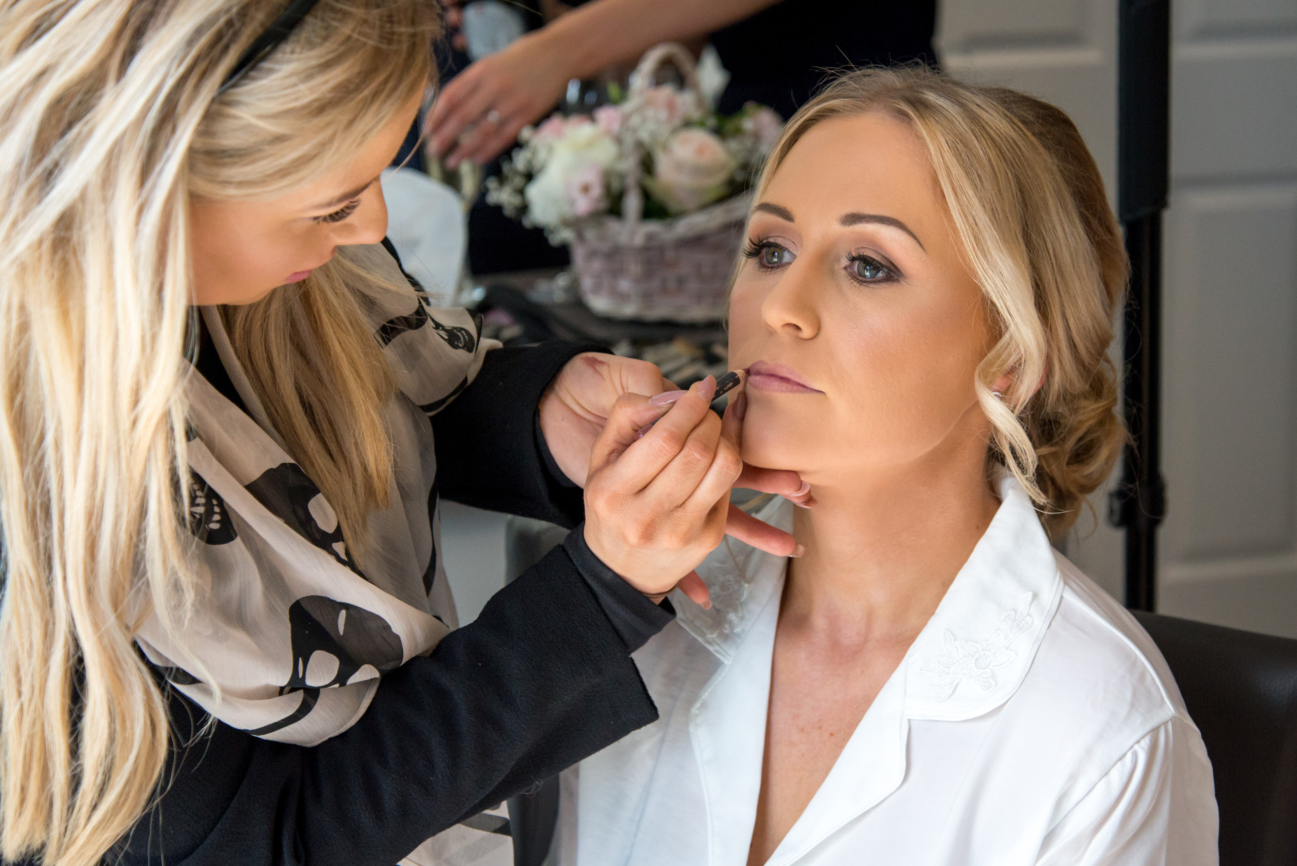 Natural candid photograph of bridal preparations of bride and make up artist applying lip gloss on morning of wedding day