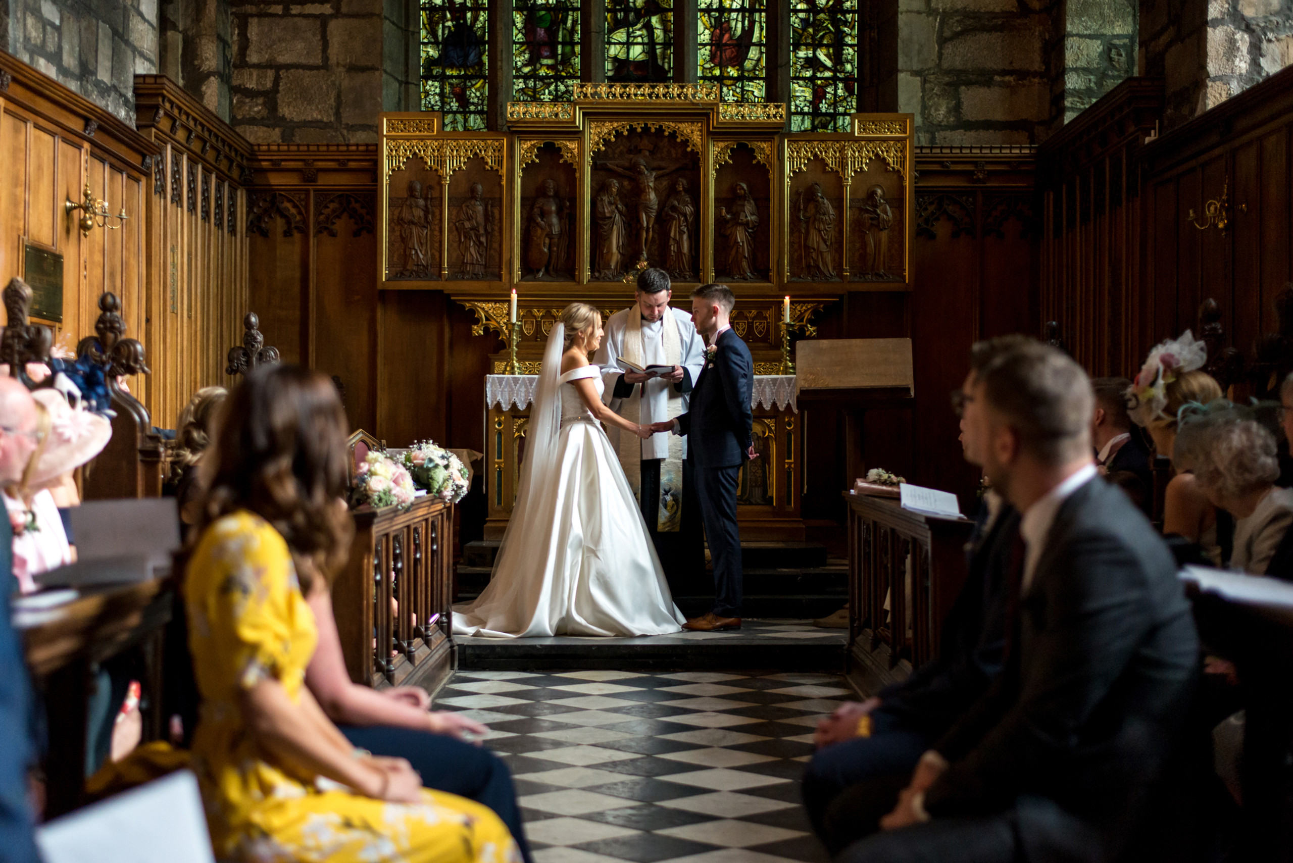Photograph of bride and groom holding hands at the altar of Tunstall Chapel of Durham Castle on day of wedding ceremony