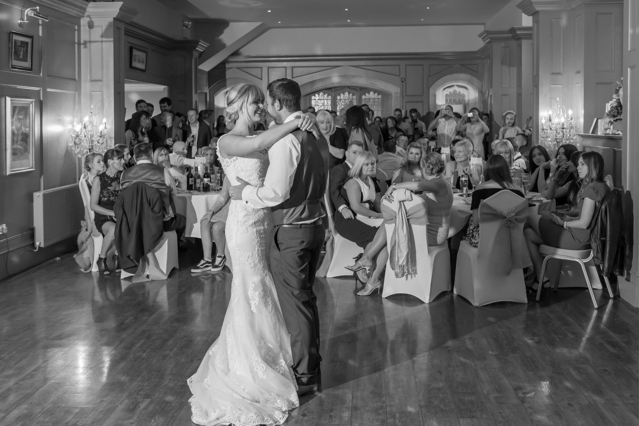 Black and white monochrome photography of bride and groom smiling during first dance at Ellingham Hall wedding venue in Northumberland