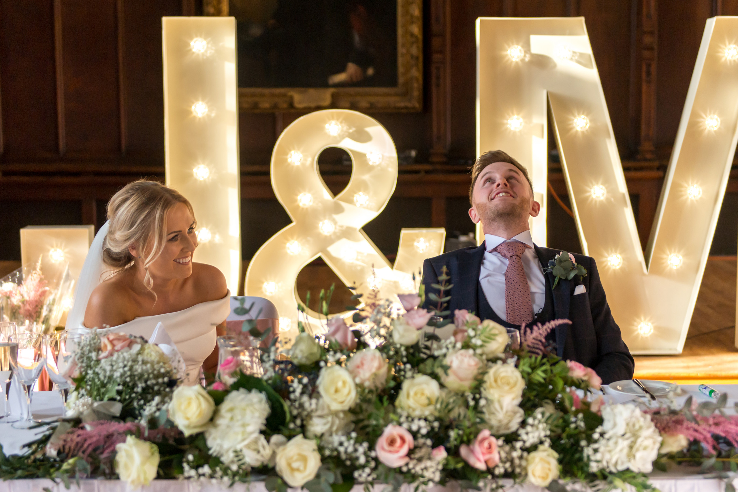 Photography of bride and groom smiling at best man's speech in Bishops Hall during wedding breakfast at historic venue Durham Castle in Durham City