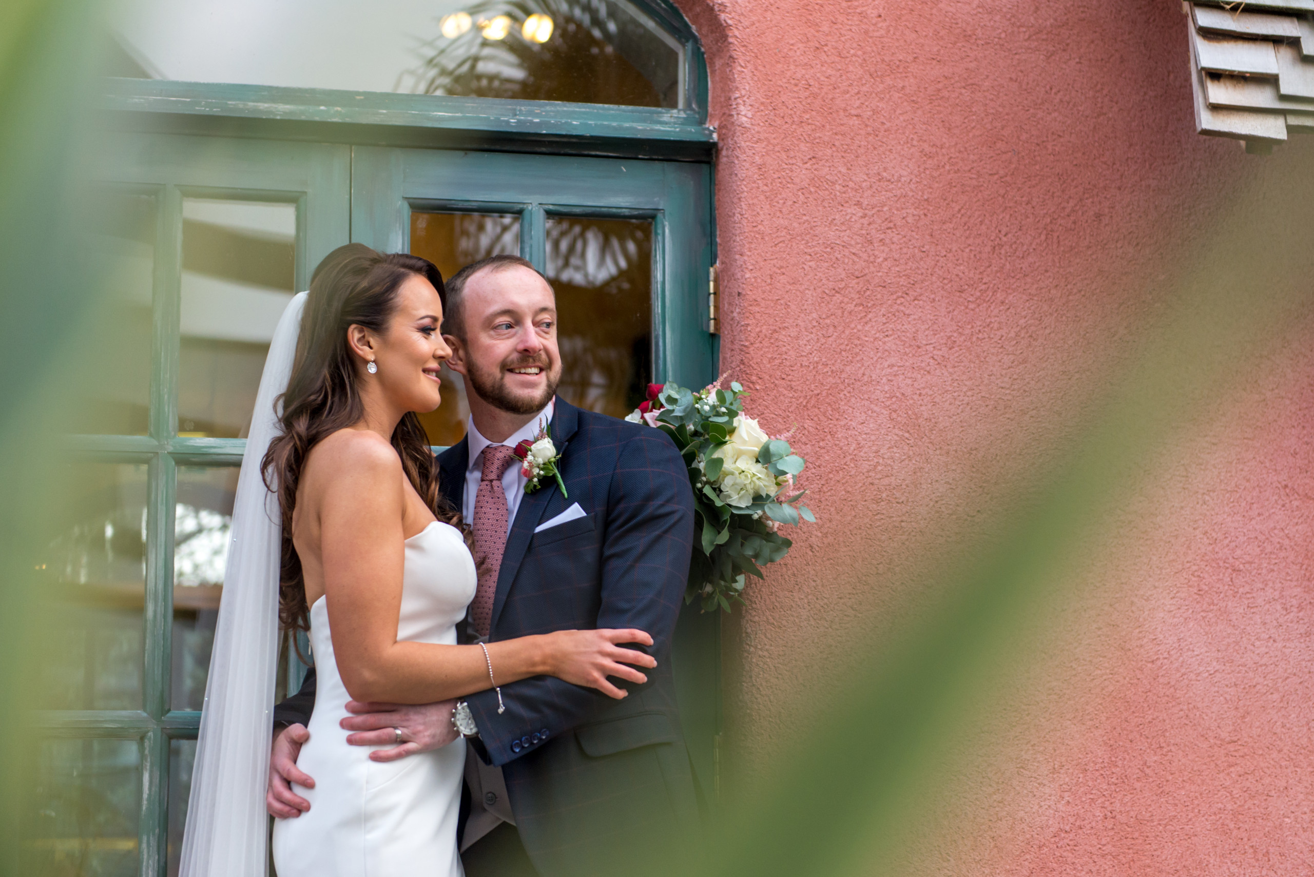 Relaxed posed photograph of bride and groom smiling on wedding day at Le Petit Chateau in Otterburn, Northumberland