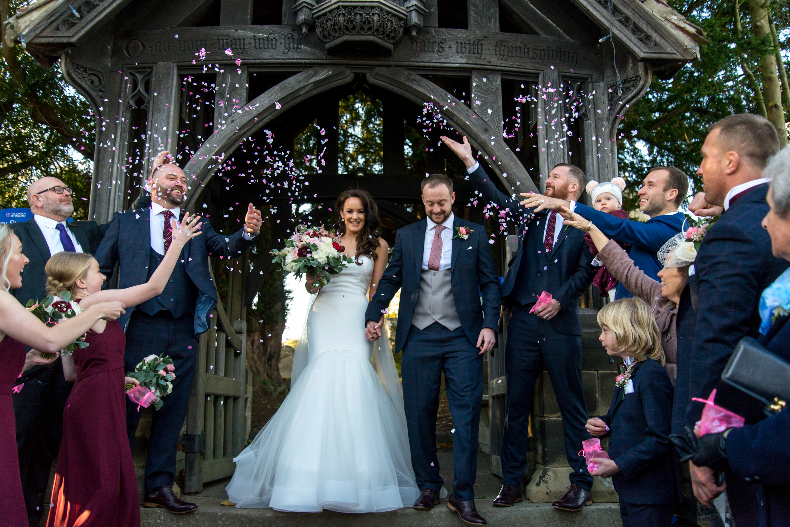 Wedding day photo of Bride and groom confetti outside of church in Stannington