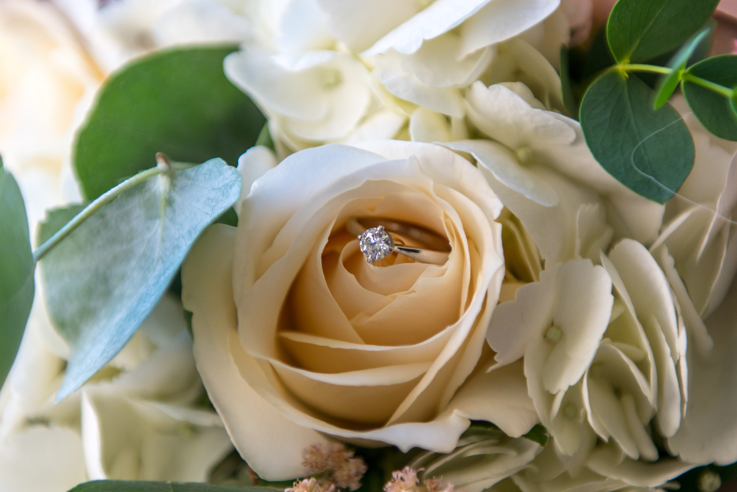 Photo of diamond engagement ring in bride's flower bouquet during wedding day preparations