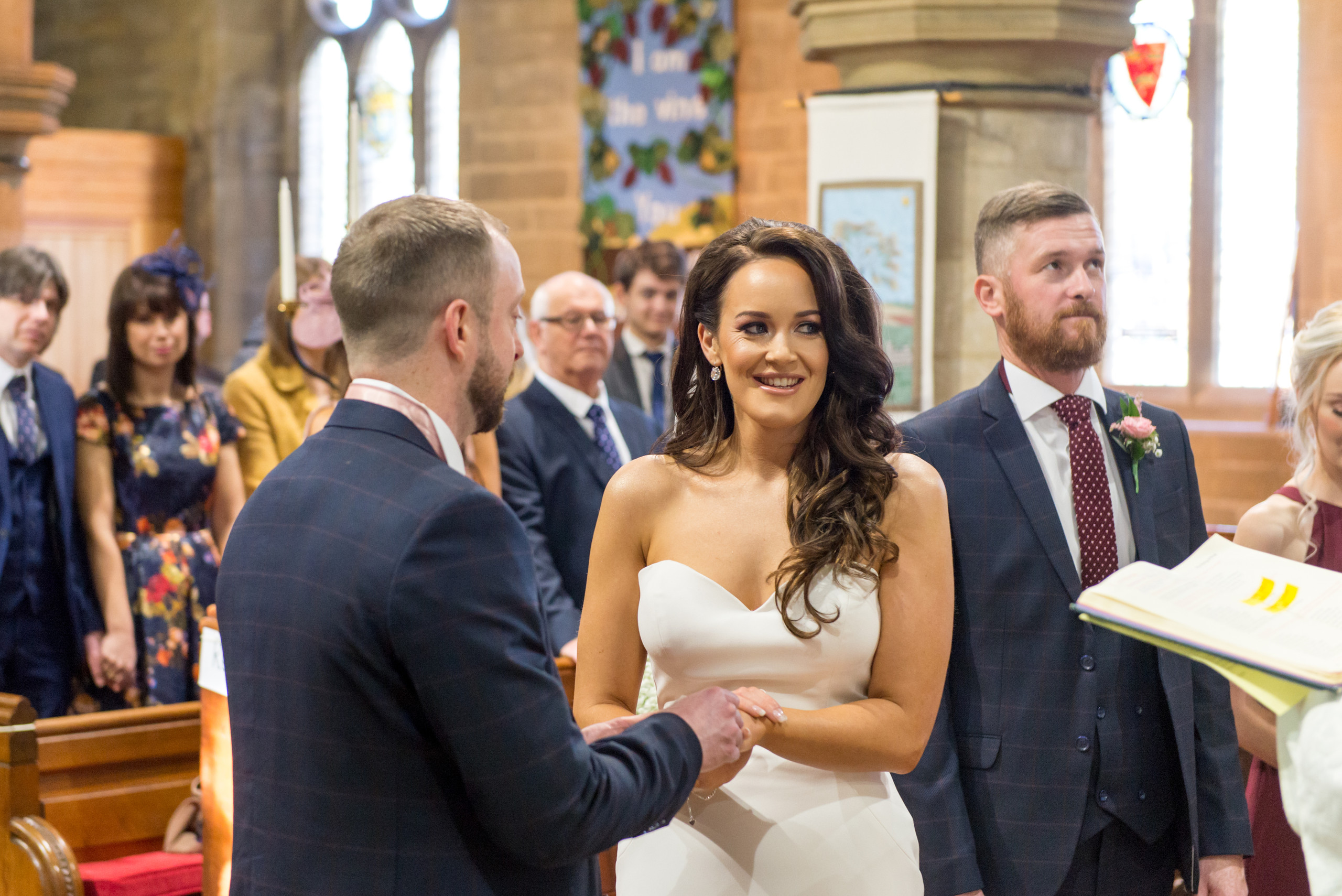 Photo of relaxed bride and groom exchanging rings during church ceremony