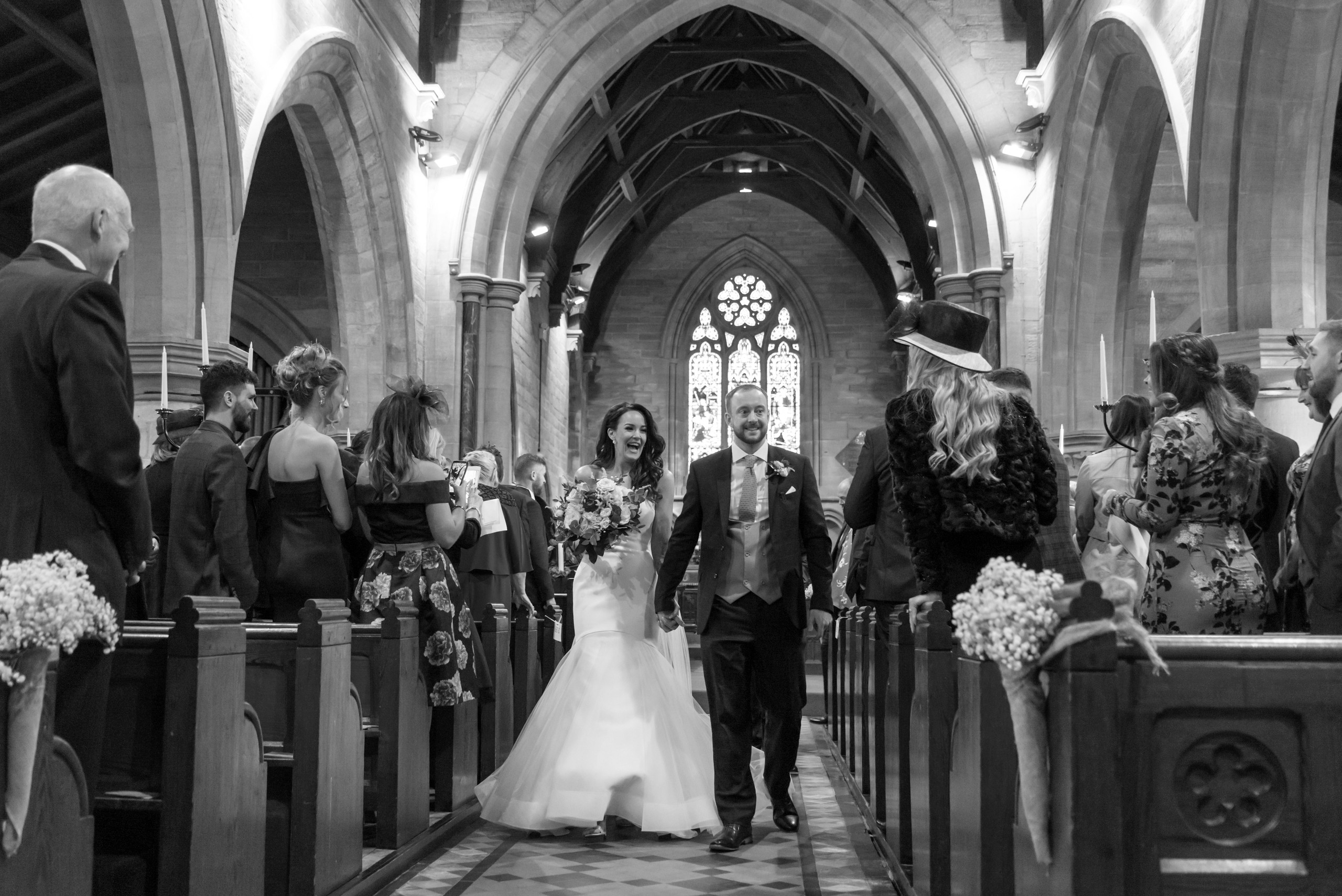 Relaxed and smiling bride and groom walking down the aisle after intimate church ceremony