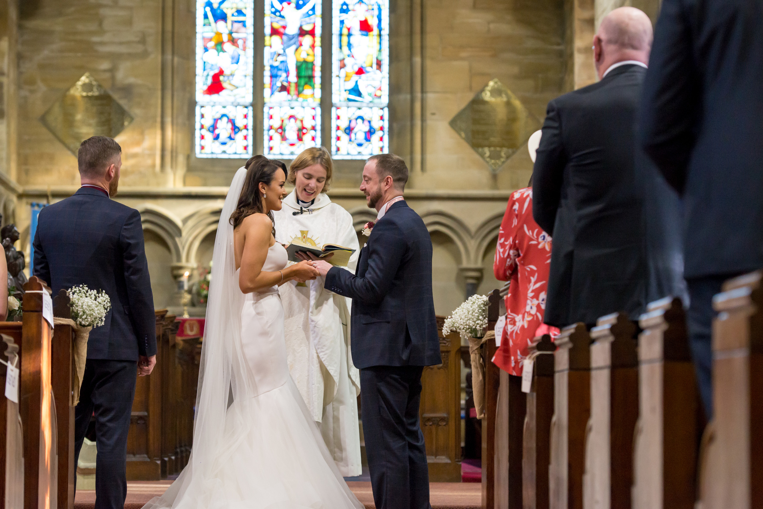 Bride and groom exchanging rings during wedding ceremony in church